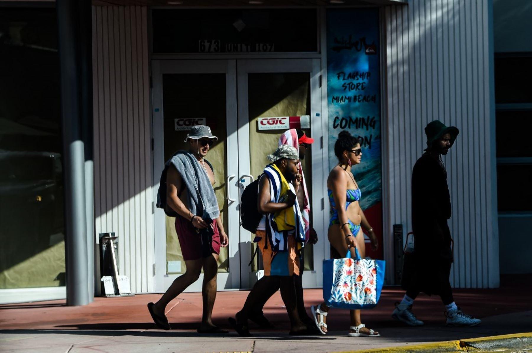 La gente camina de regreso de la playa en Miami Beach, Florida. Foto: AFP