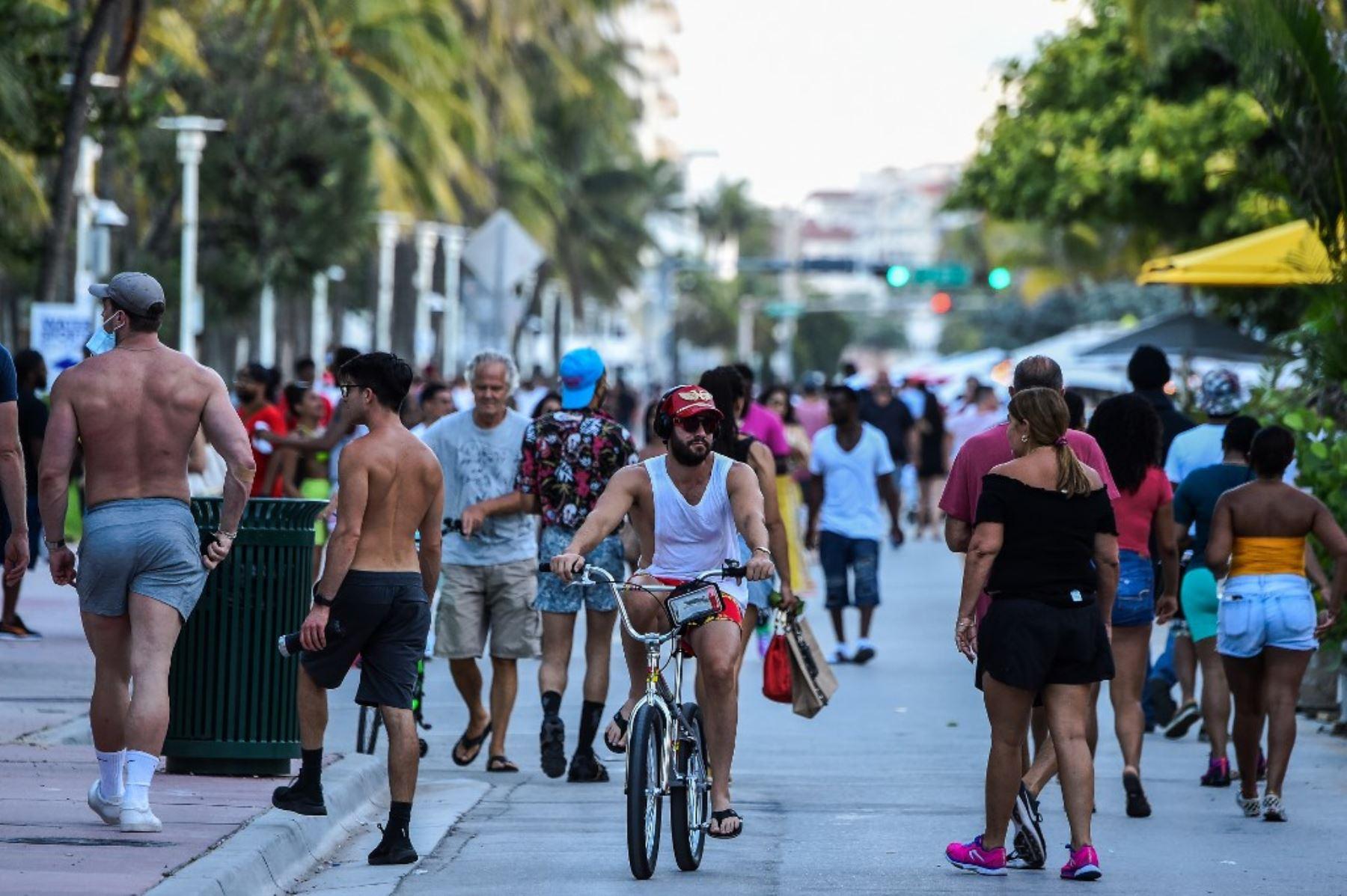 Un hombre monta una bicicleta mientras la gente camina en Ocean Drive en Miami Beach, Florida. Foto: AFP