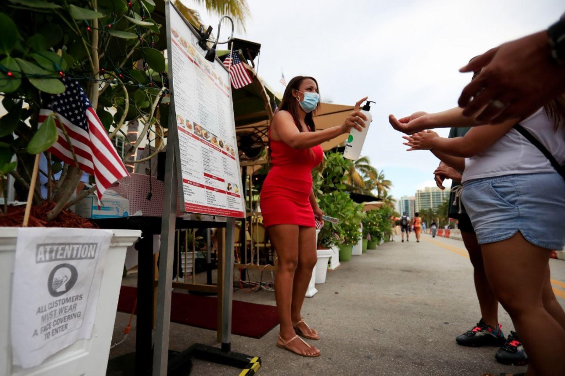 Una anfitriona proporciona desinfectante para manos a los clientes que ingresan a un restaurante en el vecindario de South Beach en Miami Beach, Florida. Foto: AFP