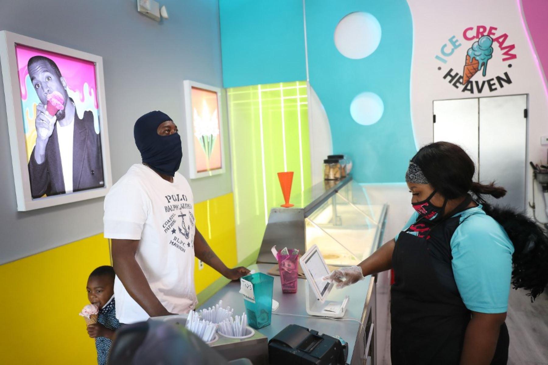 Un padre y su hijo compran helados en una tienda en Miami. Foto: AFP