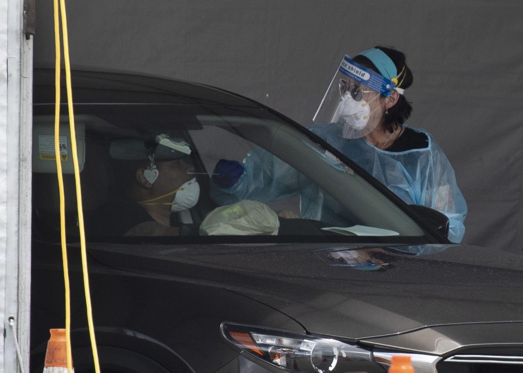 Un trabajador de salud examina a una persona por covid-19 en el sitio de prueba covid ubicado en el estacionamiento del Hard Rock Stadium en Miami. Foto: AFP