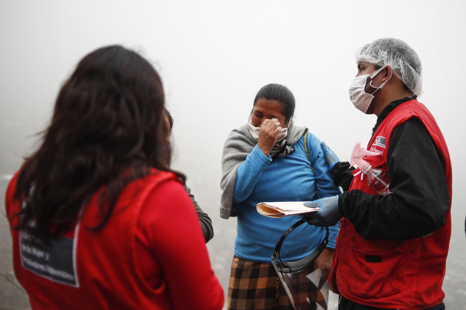 Una habitante del asentamiento humano se acerca al equipo del Inabif y se quiebra al relatar sus complicados días durante la pandemia por coronavirus. Foto. ANDINA/Renato Pajuelo