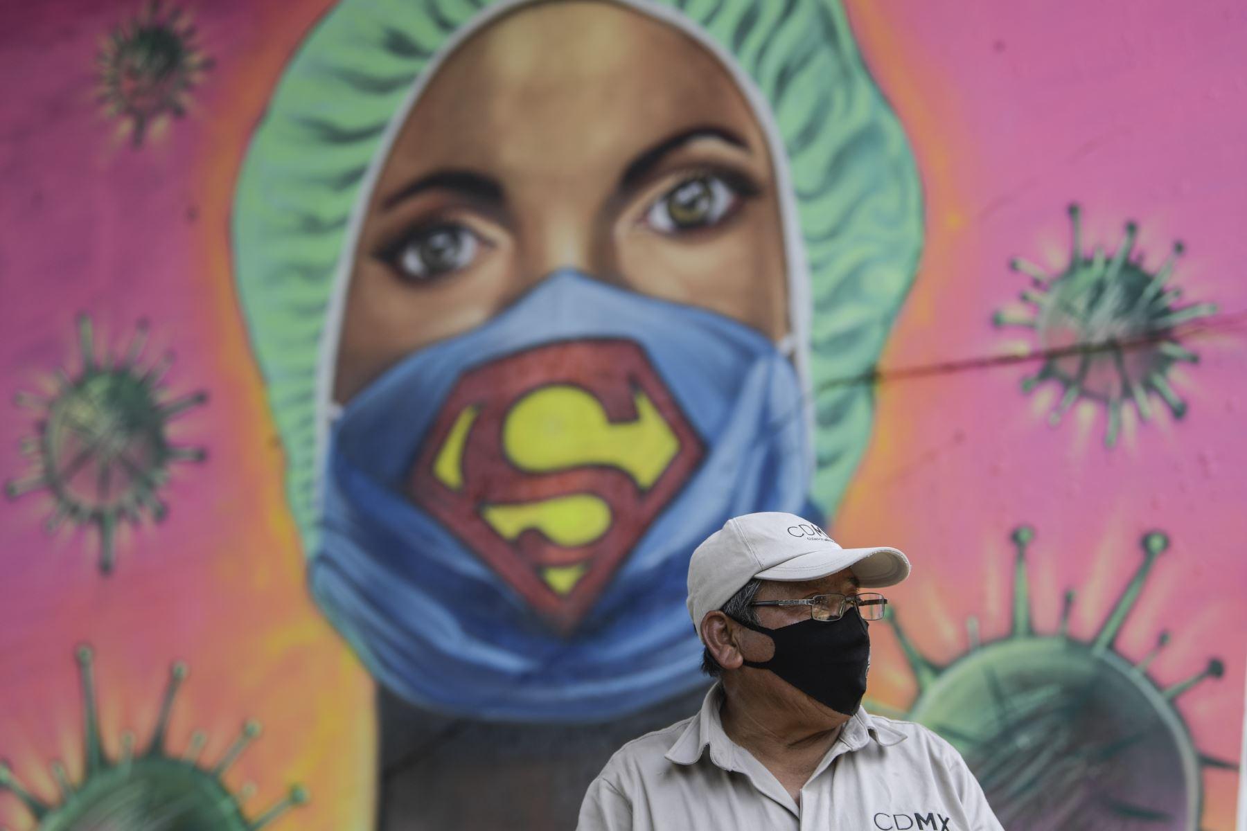 Un jardinero de la ciudad trabaja junto a un mural que muestra a un miembro de la sanidad usando una mascarilla con el símbolo del superhéroe ficticio Supermán, en Ciudad de México, en medio de la nueva pandemia del covid-19. Foto: AFP.