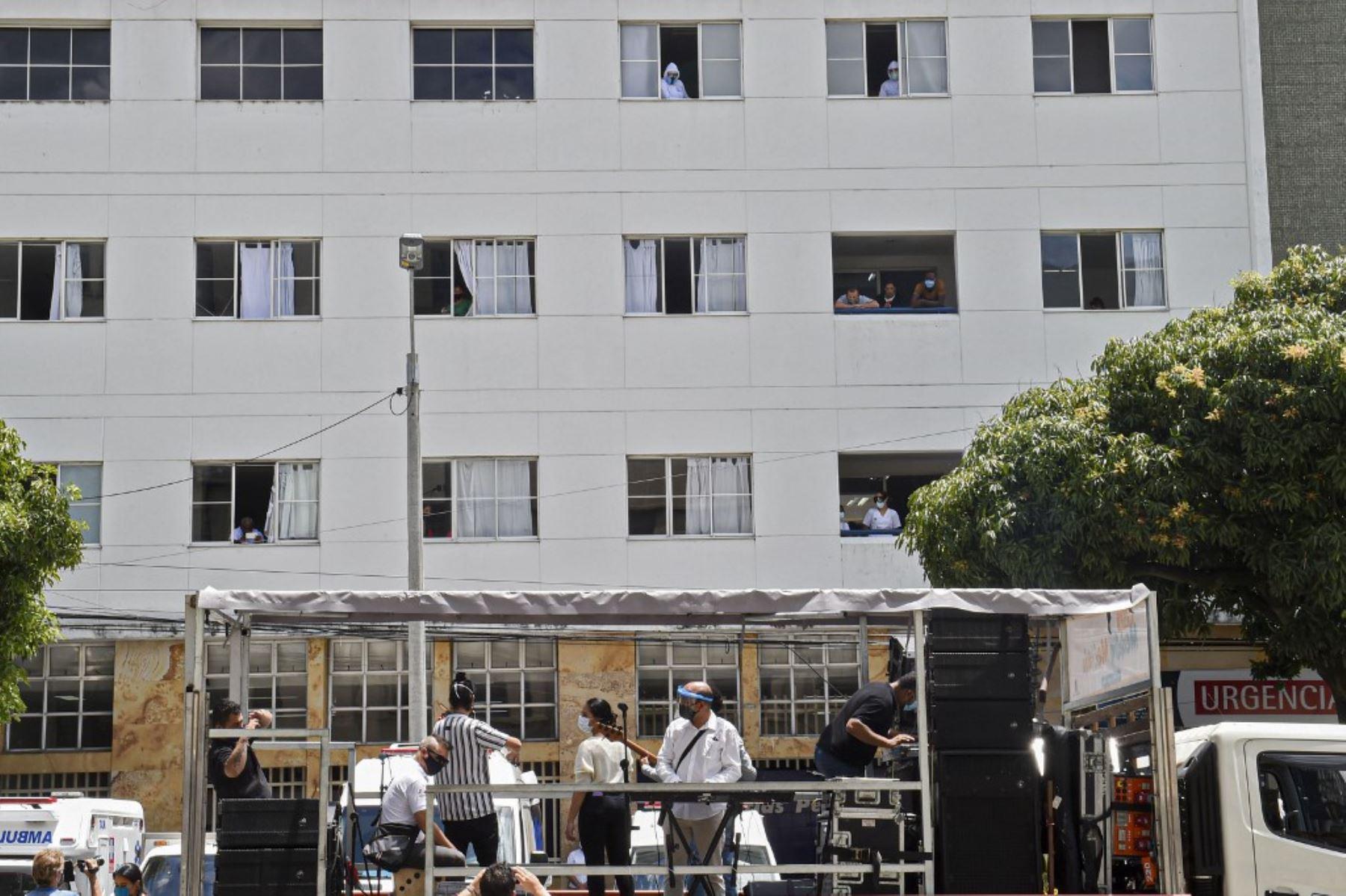 Trabajadores de la salud, pacientes y familiares miran desde las ventanas del hospital mientras una banda de música toca desde afuera en Medellín, Colombia. Foto: AFP