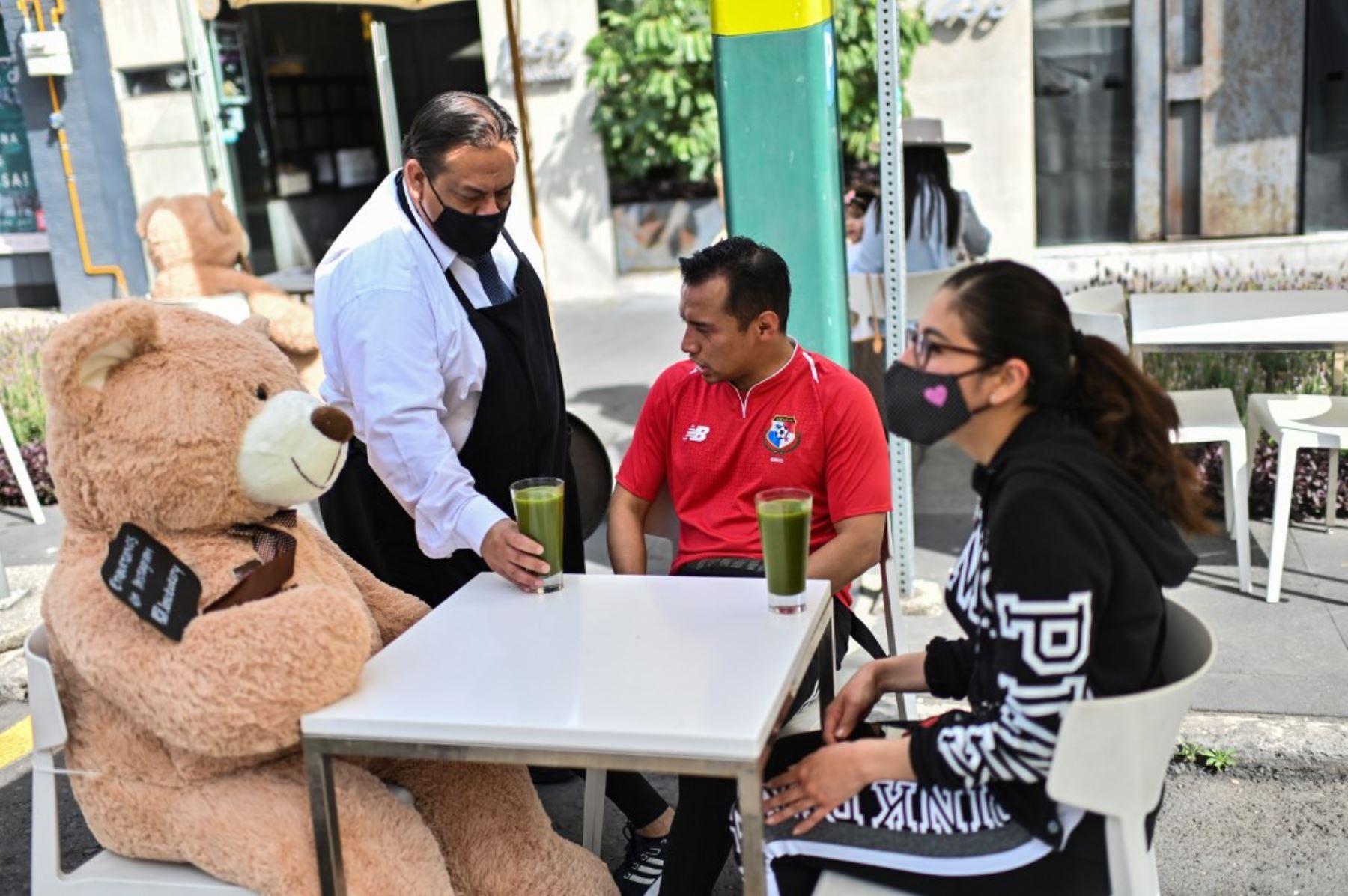 Los clientes se sientan con un oso de peluche utilizado para mantener las medidas de distanciamiento social, en un restaurante en el barrio de Polanco. Foto: AFP