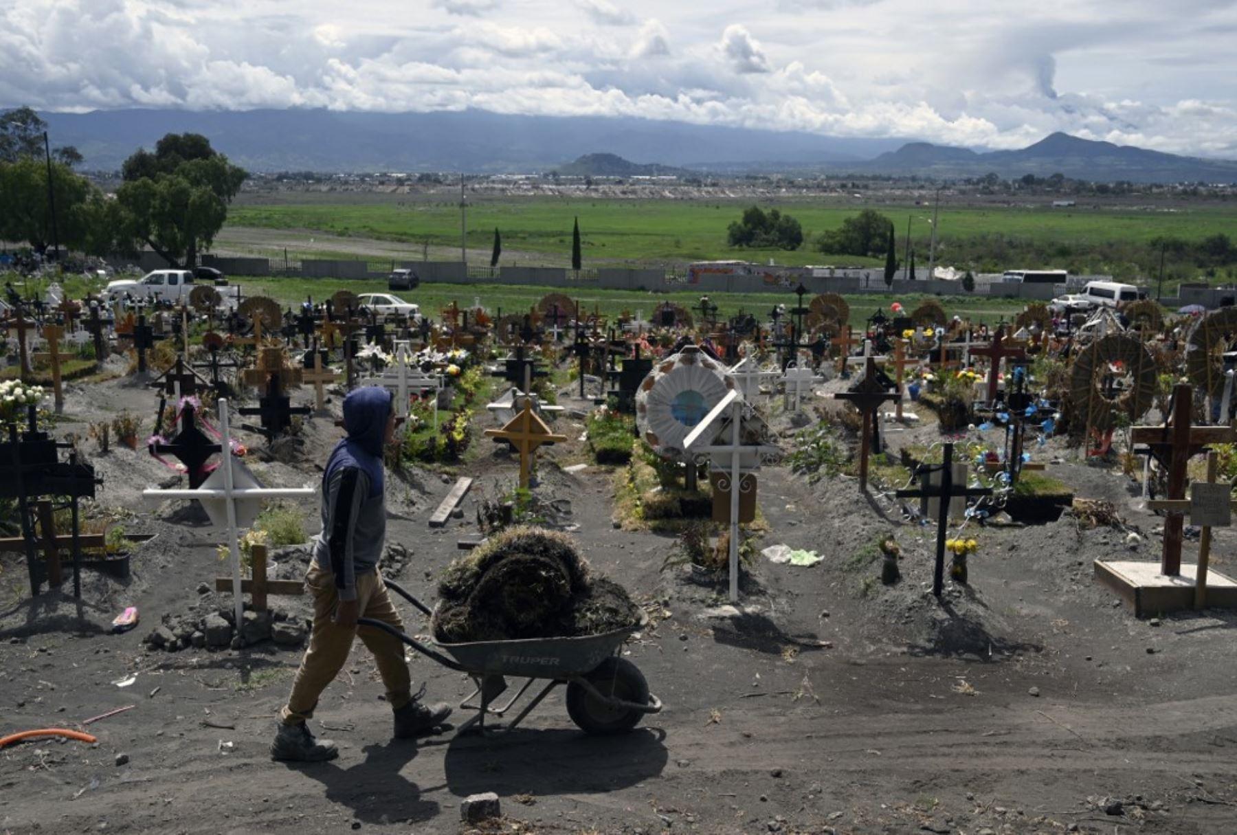 Familiares de víctimas asesinadas por covid-19 arreglan las tumbas en el área especial del Panteón Municipal del Valle de Chalco, Estado de México. Foto: AFP