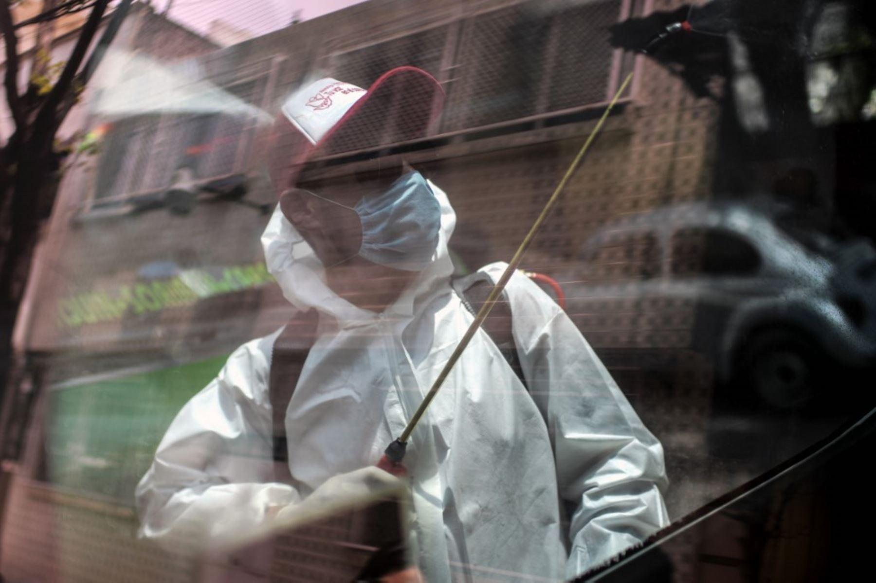 Un trabajador de limpieza con equipo de protección personal se refleja en una ventana mientras desinfecta una camioneta de transporte público en la Ciudad de México. Foto: AFP