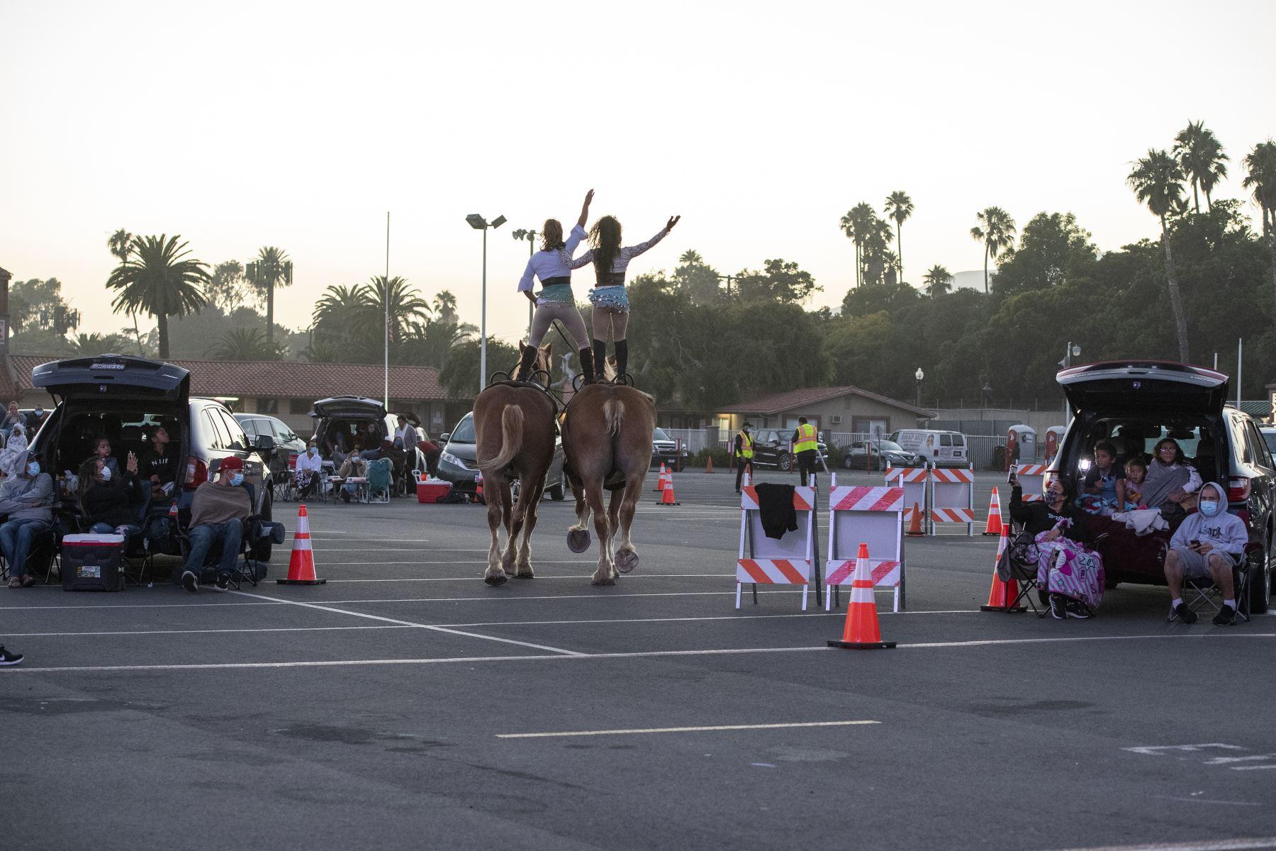 Dos artistas del Zoppe Italian Family Circus montan sus caballos entre los automóviles durante el evento en vivo