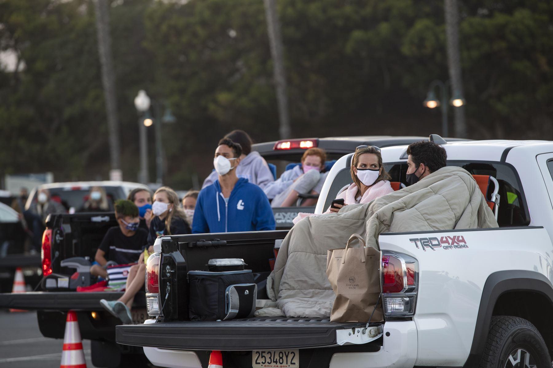 Familias aprecian el espectáculo de circo desde sus vehículos aparcados en el estacionamiento de Ventura, en California. Foto: AFP