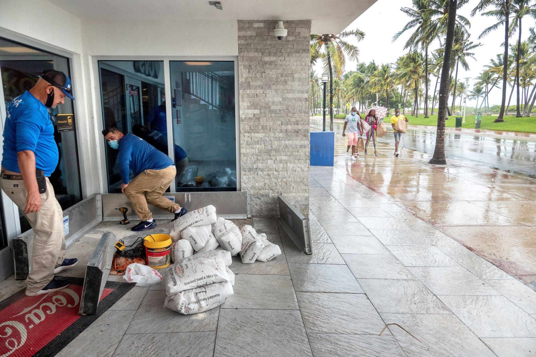 Trabajadores instalan paneles y bolsas de arena como contención en la entrada de una farmacia en Miami Beach, Florida; ante el paso del Huracán Isaías. Foto: EFE