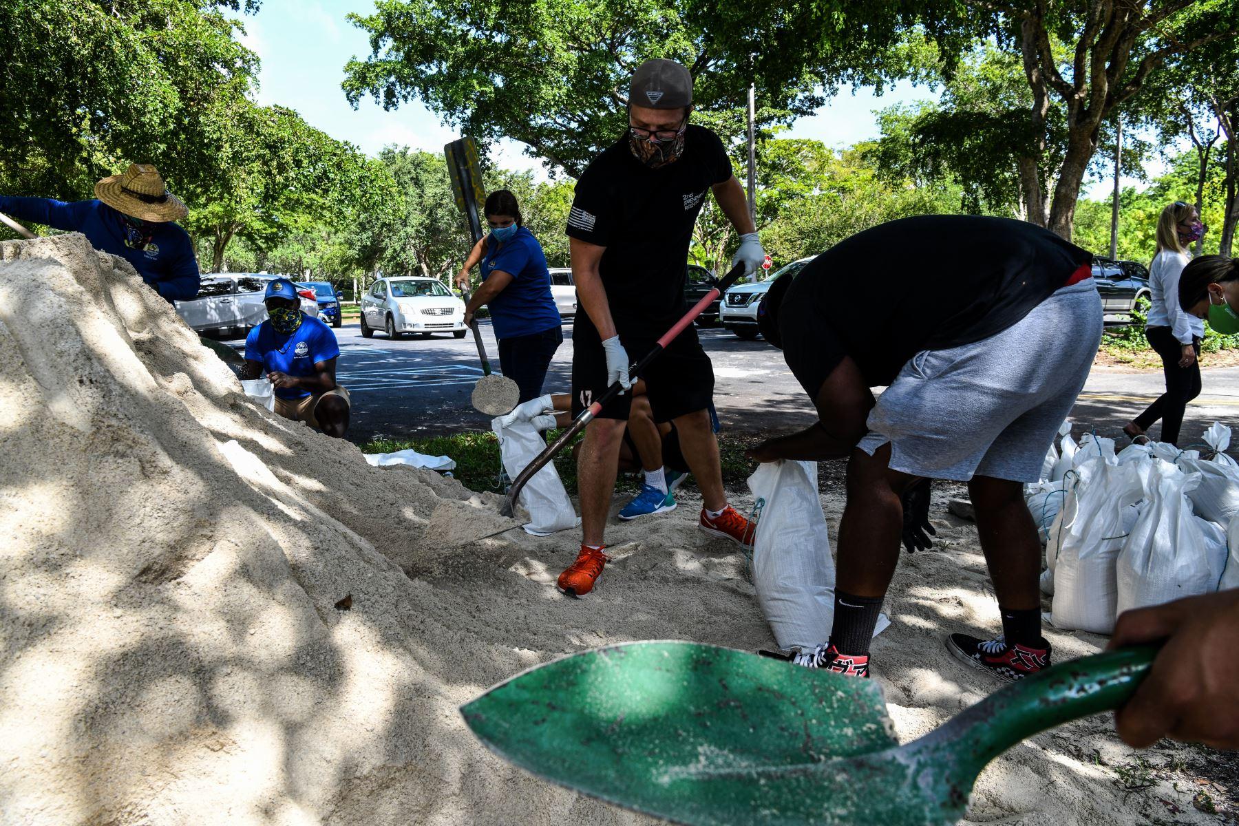 Un grupo de personas llena bolsas de arena para distribuirlas a los residentes de la Bahía de Palmetto cerca de Miami y así tratar de contener los estragos del Huracán Isaías. Foto: AFP