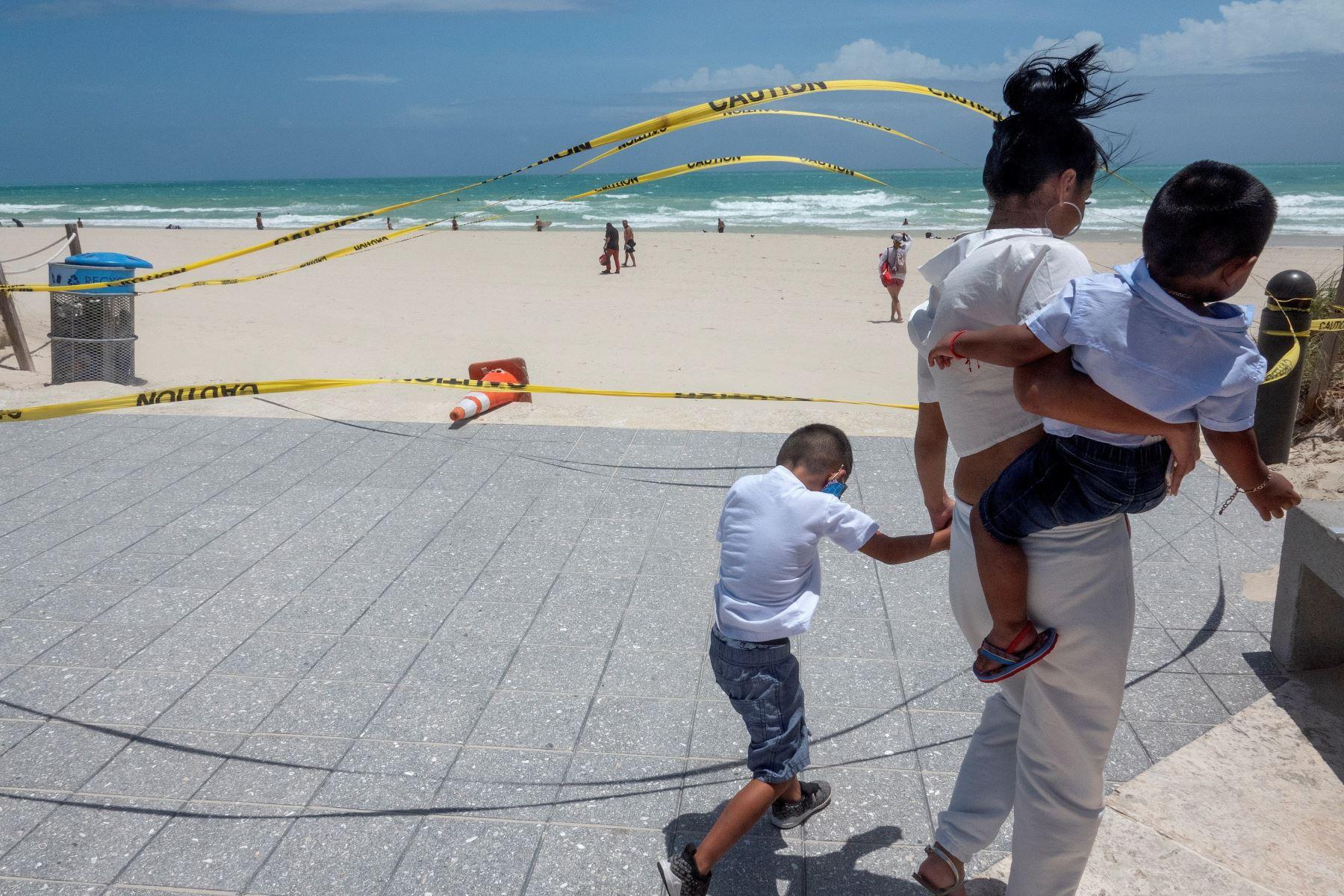 Una mujer camina junto a sus hijos por las playas de Miami, Florida, ante la pronta llegada del huracán Isaías. Foto: EFE