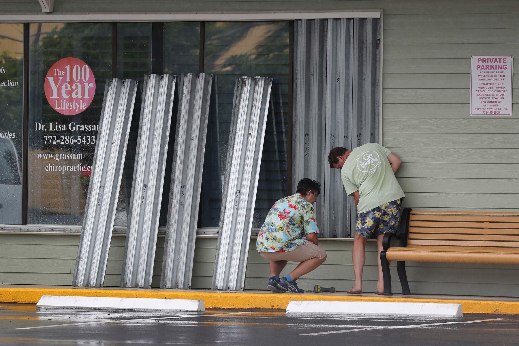 Dos hombres protegen las ventanas de sus negocios a medida que se acerca la el huracán Isaias. Foto: AFP