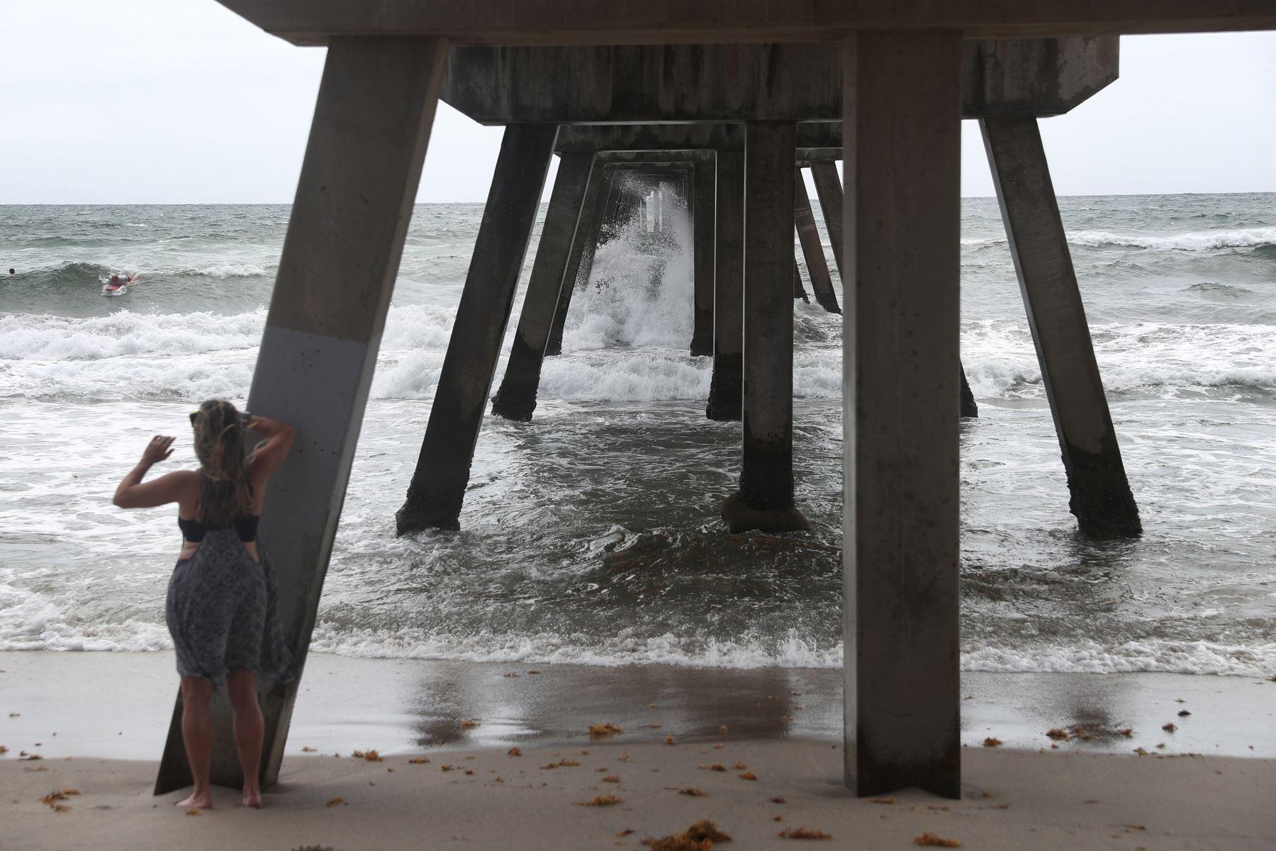 Una mujer filma a los surfistas que practican este deporte por crecida de las olas, en Deerfield Beach, Florida. Foto: AFP