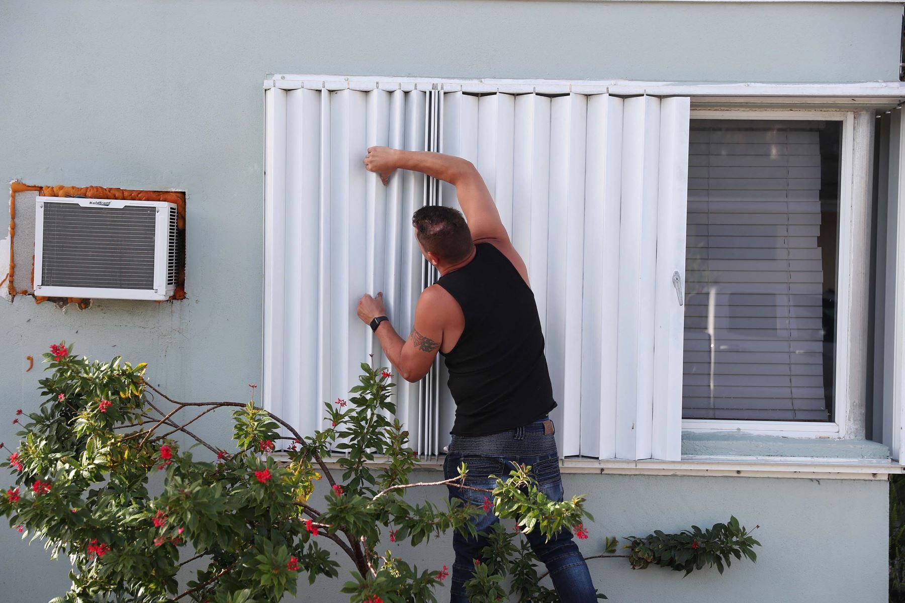 Un hombre protege las ventanas de su vivienda en Lake Worth, Florida, ante el paso del huracán Isaías. Foto: AFP