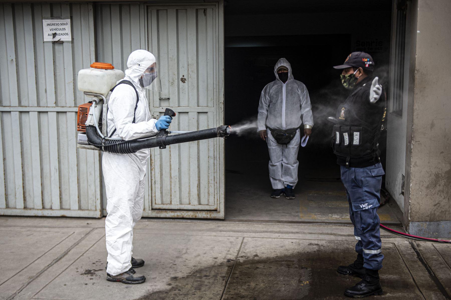 Un trabajador municipal desinfecta a un guardia de seguridad en Villa María del Triunfo. Foto: AFP