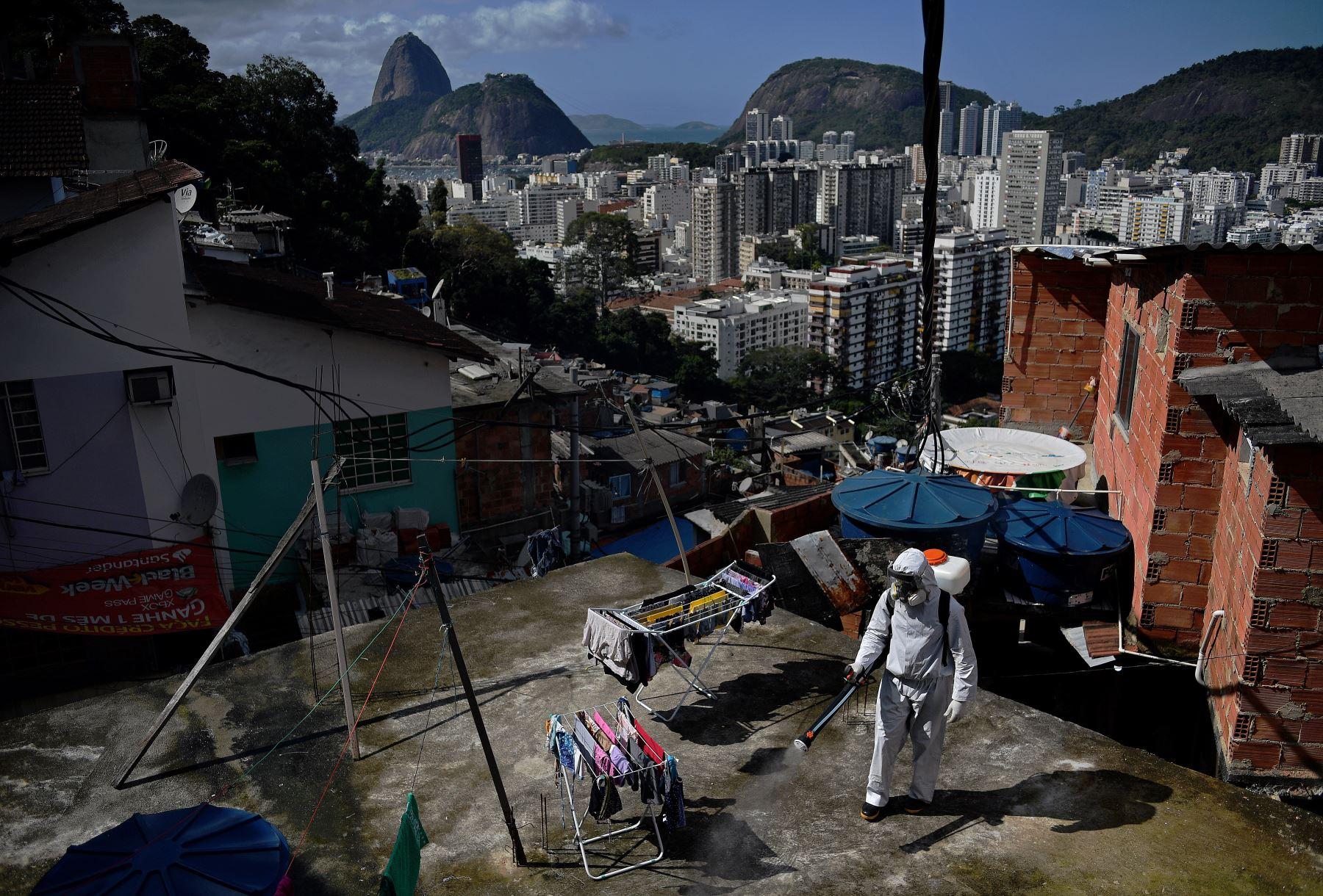 Un voluntario desinfecta un área de la azotea dentro de Santa Marta Favela, en Río de Janeiro, Brasil. Foto: AFP