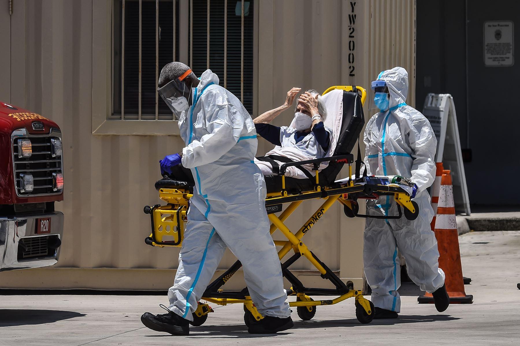 Los médicos transfieren a un paciente en una camilla desde una ambulancia afuera de Emergencia en el Hospital Coral Gables, cerca a Miami. Foto: AFP