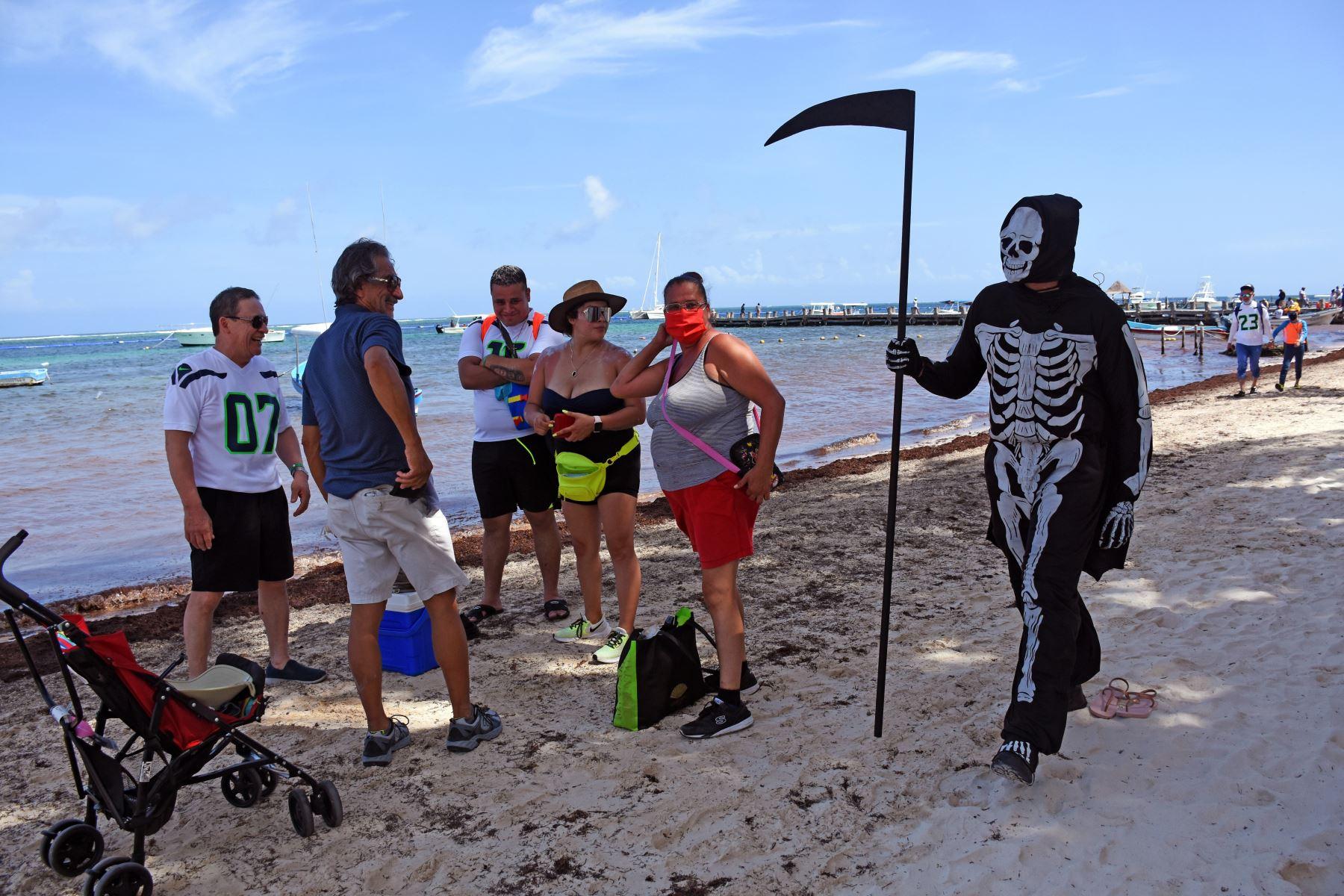 Un joven representa a la muerte invitando a turistas y lugareños a regresar a sus hogares ya que las playas  de México aún están cerradas para los visitantes debido a la pandemia. Foto: AFP