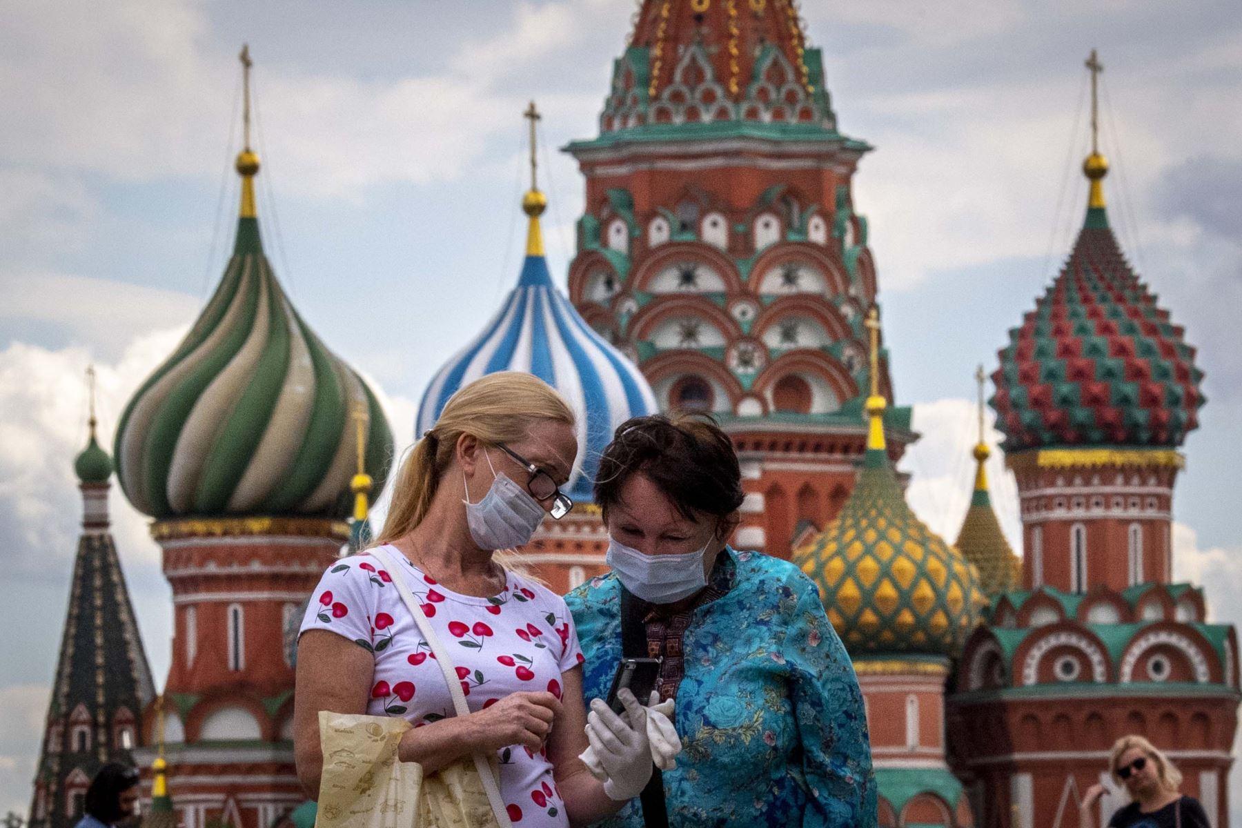 Dos mujeres con máscaras observan la pantalla de un teléfono frente a la Catedral de San Basilio en el centro de Moscú, Rusia. Foto: AFP