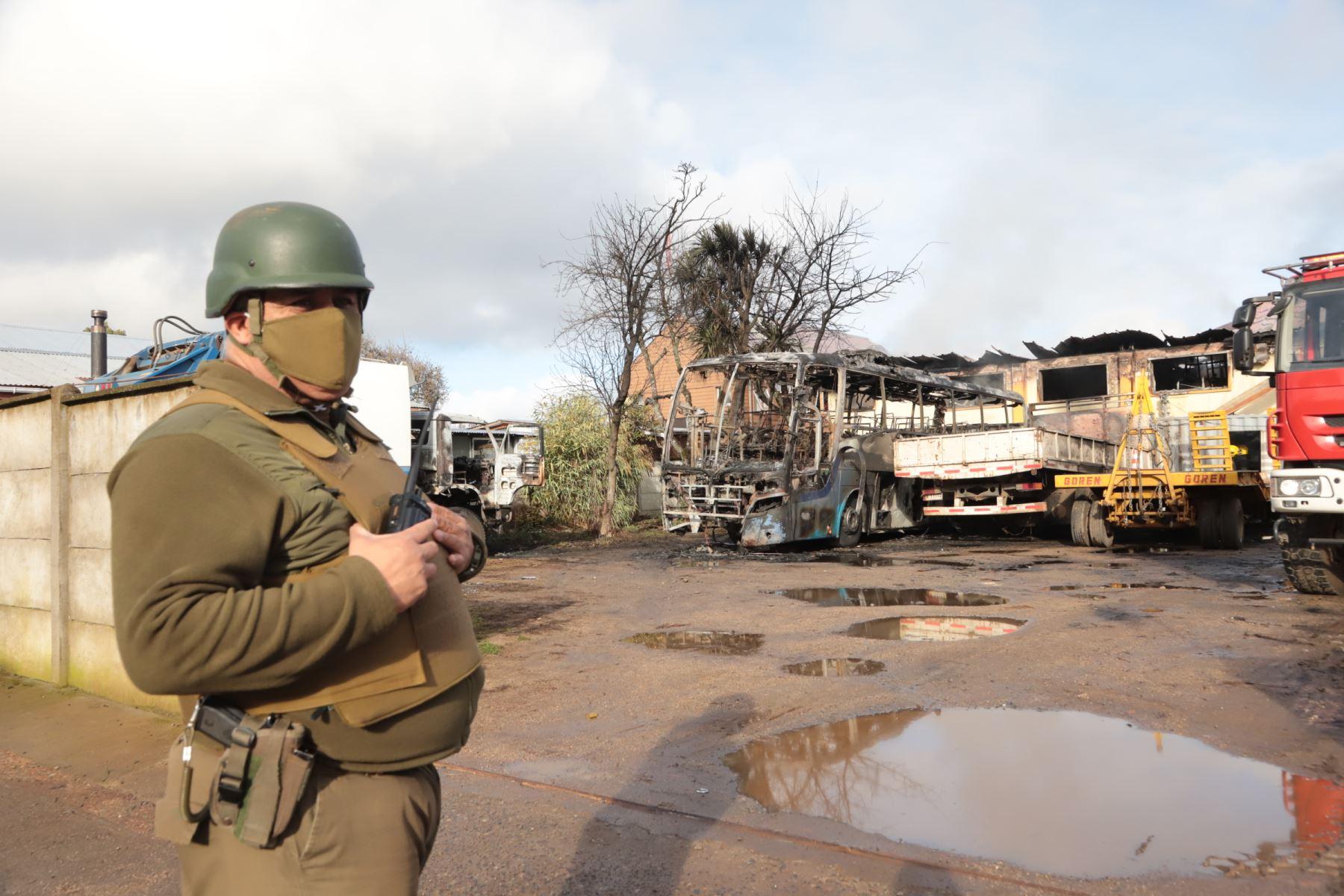 Un guardia de policía junto a vehículos incendiados frente al municipio de Ercilla, región de la Araucanía, sur de Chile. Foto: AFP