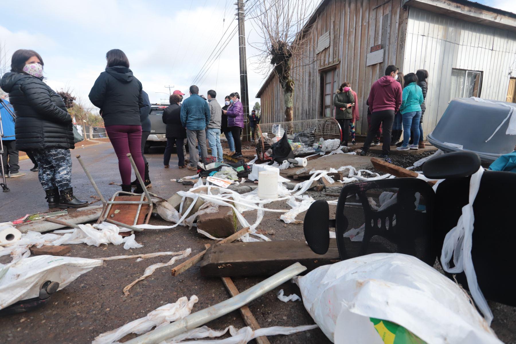 Un grupo de vecinos observan los daños frente al municipio de Ercilla, región de la Araucanía, sur de Chile después de que fue destruido durante las protestas. Foto: AFP