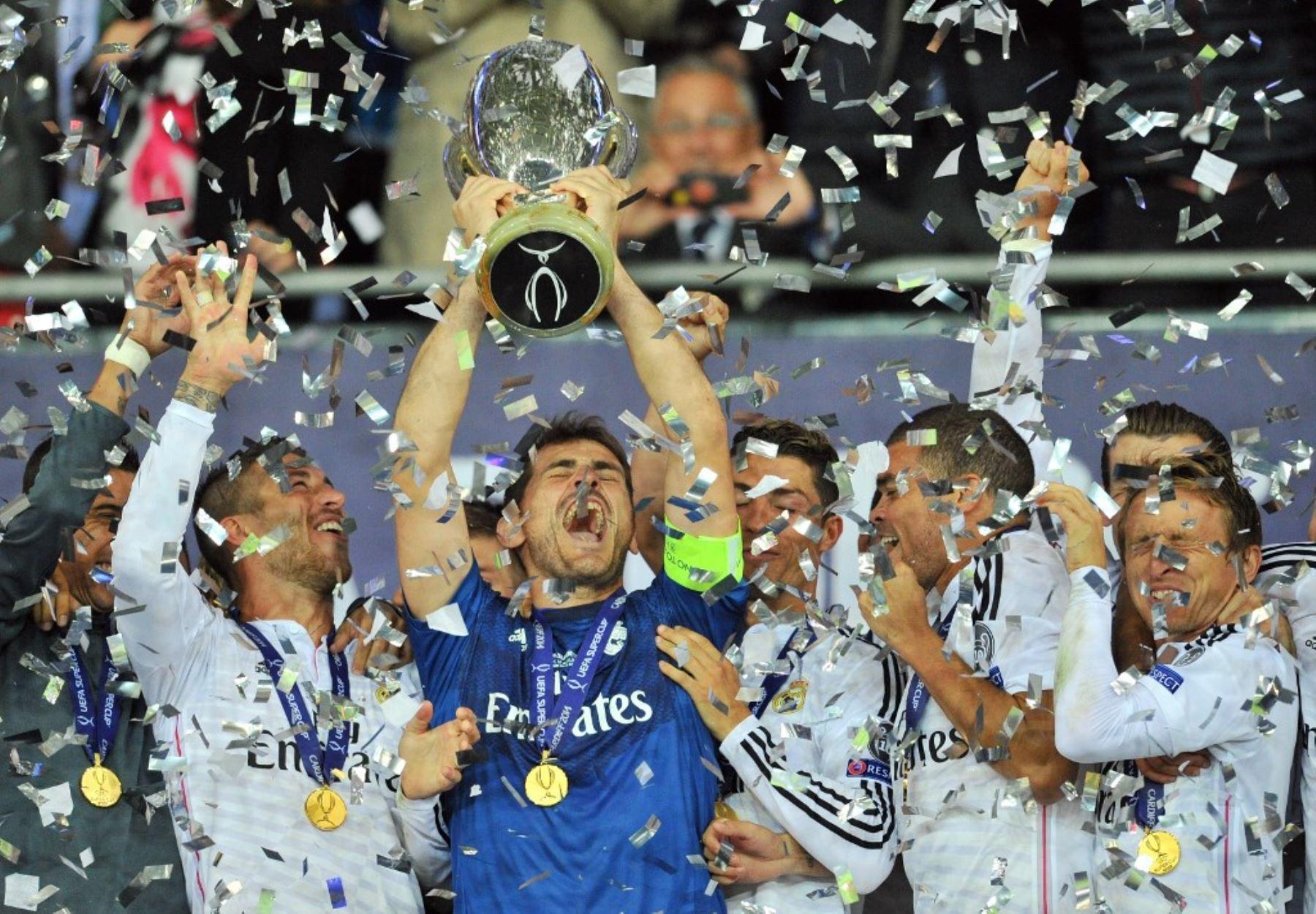 El portero del Real Madrid, Iker Casillas, levanta el trofeo mientras los jugadores del Real Madrid celebran después del partido de fútbol de la Supercopa de la UEFA entre el Real Madrid y el Sevilla. Foto: AFP