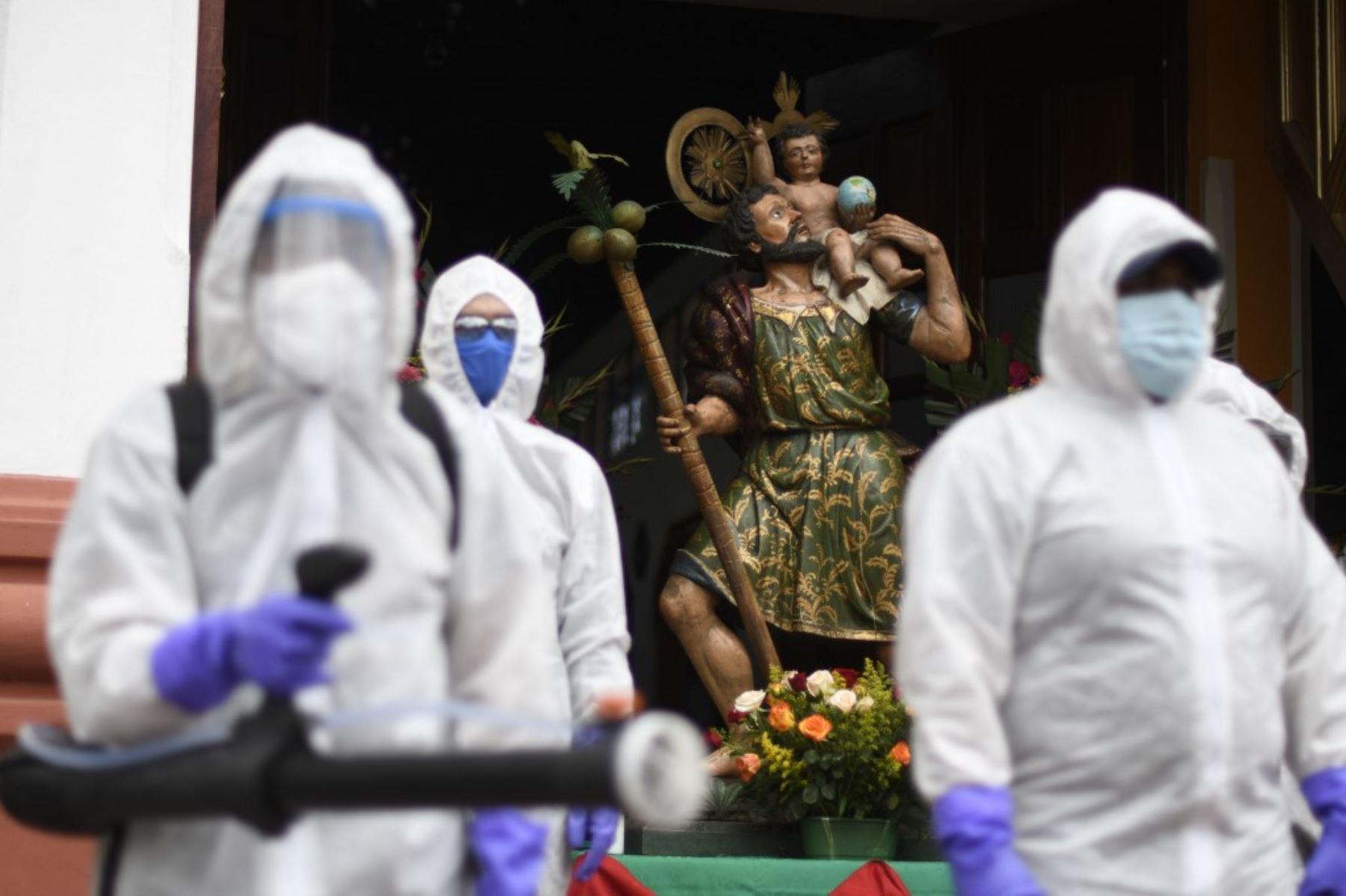 Los trabajadores municipales en traje de protección se preparan para desinfectar un automóvil fuera de una iglesia durante la celebración del Día de San Cristóbal, patrón de viajeros y conductores, en la Ciudad de Guatemala. Foto: AFP