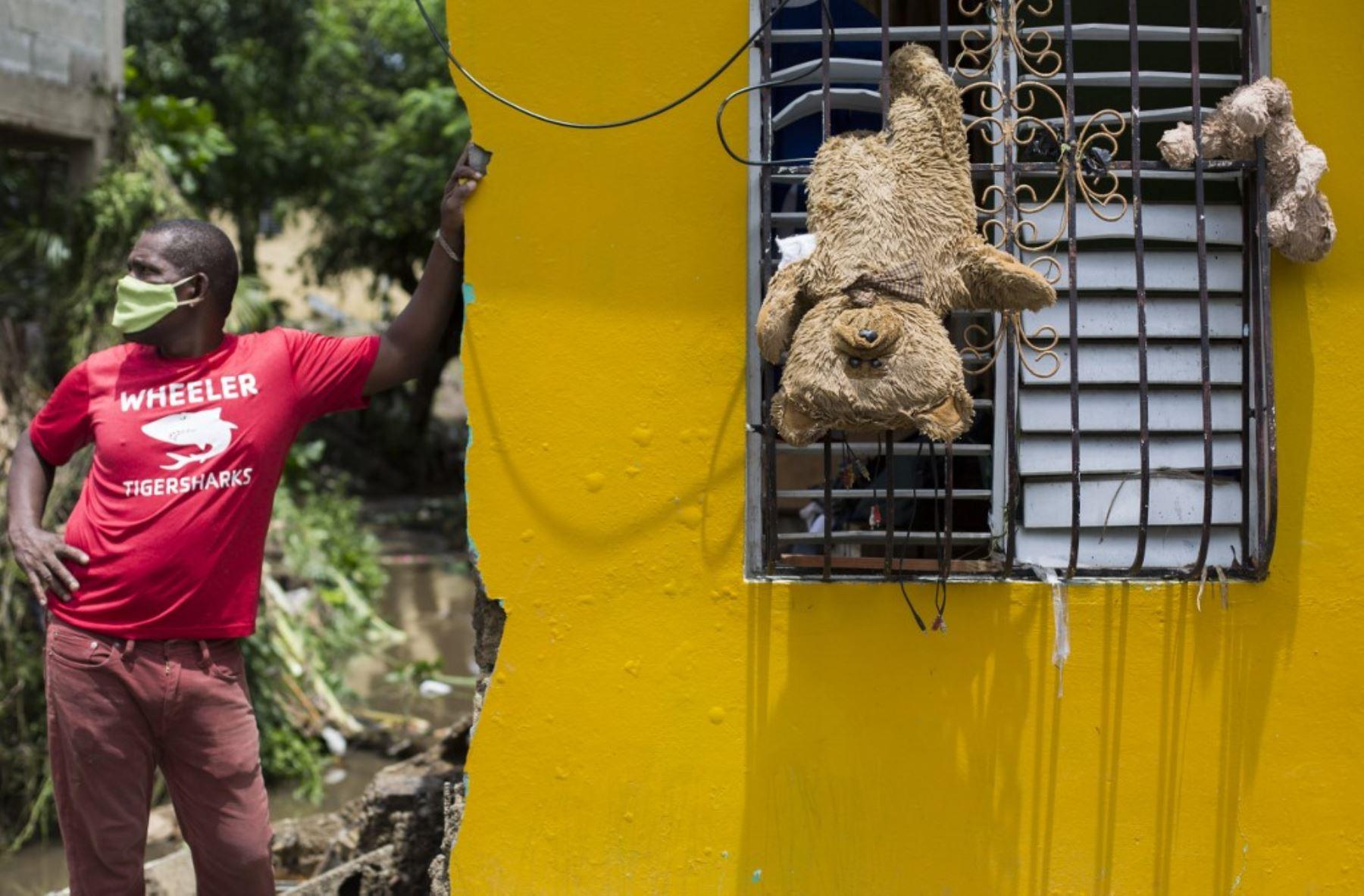 Un hombre permanece afuera de su casa, donde colgaron a los ositos de peluche desde una ventana para que se secasen después del paso de la tormenta tropical Isaias, con las que fuertes lluvias causaron el desbordamiento del río Magua en Hato Mayor, República Dominicana. Foto: AFP