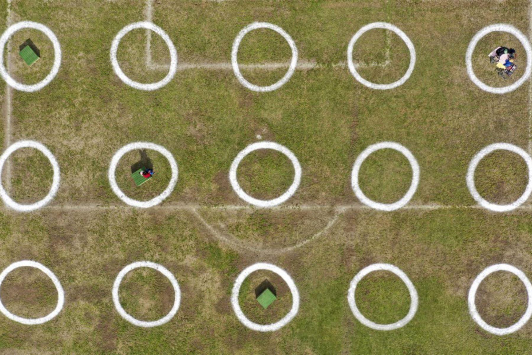 Vista aérea de personas en un campo con círculos pintados como marcadores para mantener una distancia social segura en Santiago, Chile. Foto: AFP