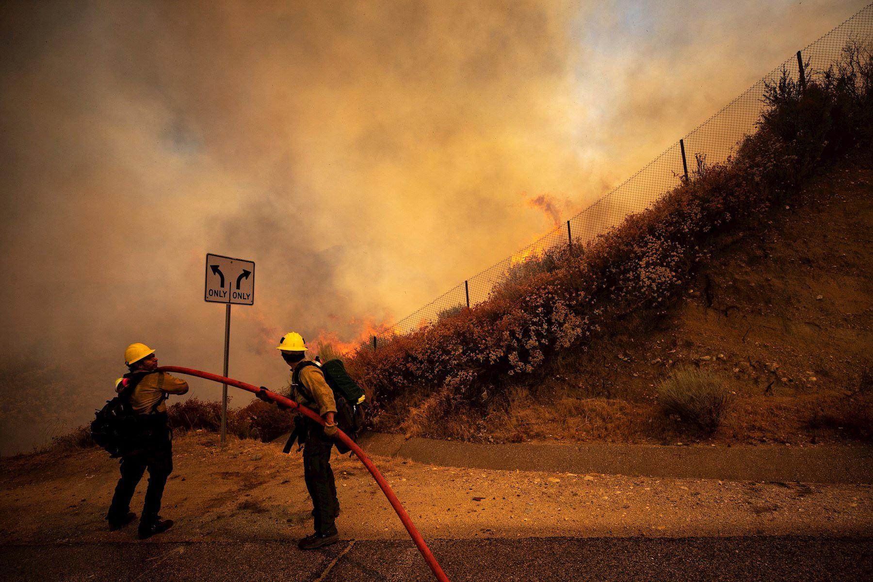 Dos bomberos intentan extinguir el incendio de Elsmere cerca de Santa Clarita, California, EE. UU. Según los últimos informes de los medios, el incendio ha quemado 130 acres. Foto: EFE