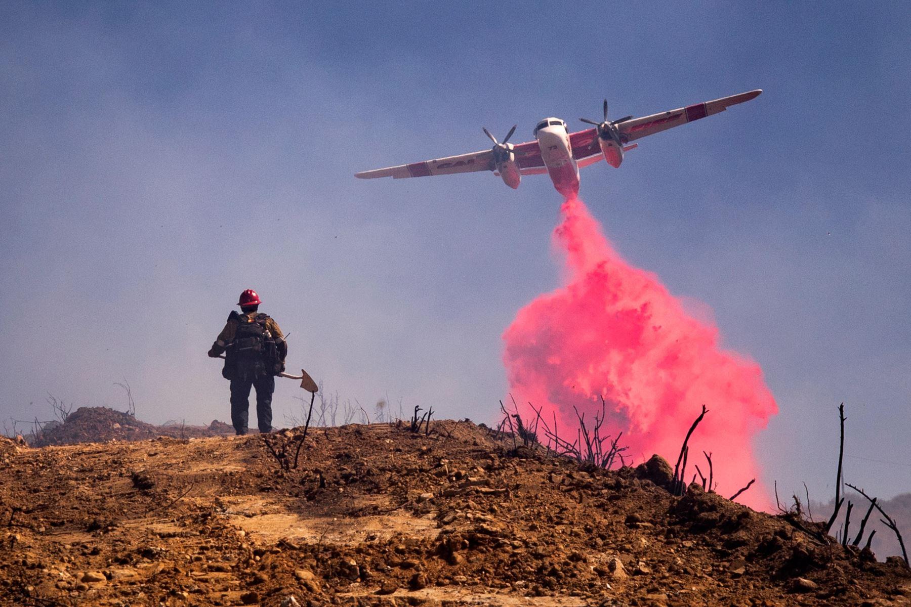 Un avión vuela sobre un bombero y arroja retardante de fuego en Elsmere Fire cerca de Santa Clarita, California, EE. UU. Según los últimos informes de los medios, el incendio ha quemado 130 acres.  Foto: EFE