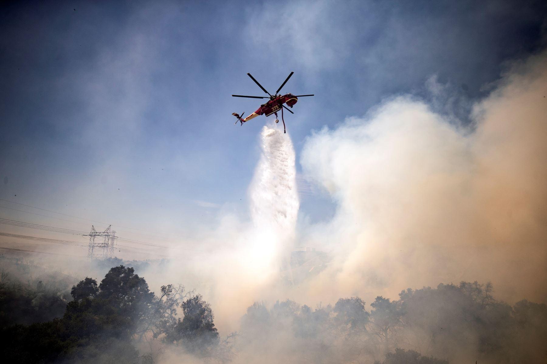 Un helicóptero arroja agua sobre el incendio de Elsmere cerca de Santa Clarita, California, EE. UU. Según los últimos informes de los medios, el incendio ha quemado 130 acres.  Foto: EFE