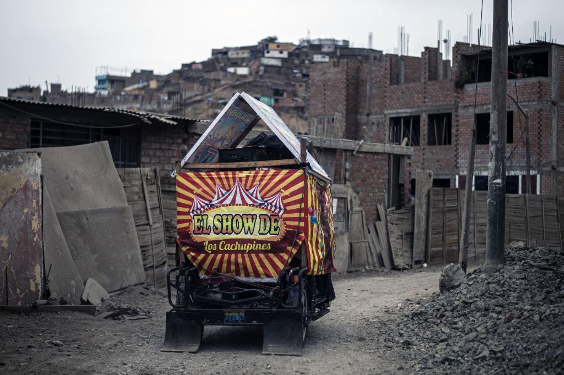 Payasos conducen su mototaxi de circo después de actuar en el distrito de Puente Piedra, en las afueras del norte de Lima, durante la pandemia covud-19. Debido a la pandemia de coronavirus, los circos en Perú permanecen cerrados, lo que lleva a este grupo de payasos que viajan en su circo mototaxi a actuar en las calles de Lima.   Foto: AFP