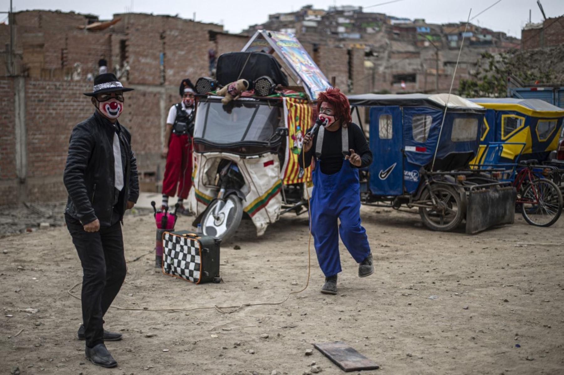 Los payasos con máscaras se presentan en el distrito de Puente Piedra, en las afueras del norte de Lima, durante la pandemia covid-19. Debido a la pandemia de coronavirus, los circos en Perú permanecen cerrados, lo que lleva a este grupo de payasos que viajan en su circo mototaxi a actuar en las calles de Lima.   Foto: AFP