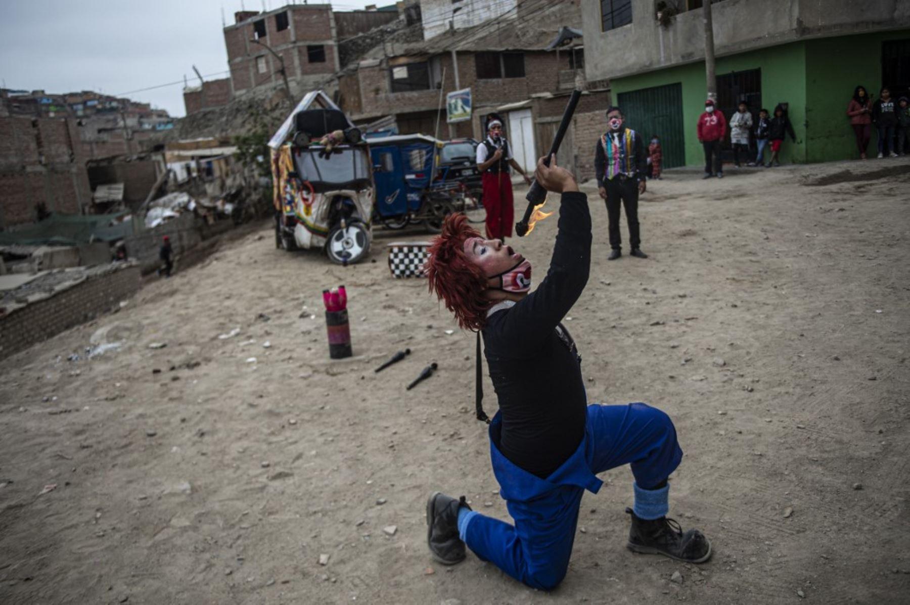 Un payaso actúa en el distrito de Puente Piedra, en las afueras del norte de Lima, durante la pandemia de covid-19. Debido a la pandemia de coronavirus, los circos en Perú permanecen cerrados, lo que lleva a este grupo de payasos que viajan en su circo mototaxi a actuar en las calles de Lima.   Foto: AFP