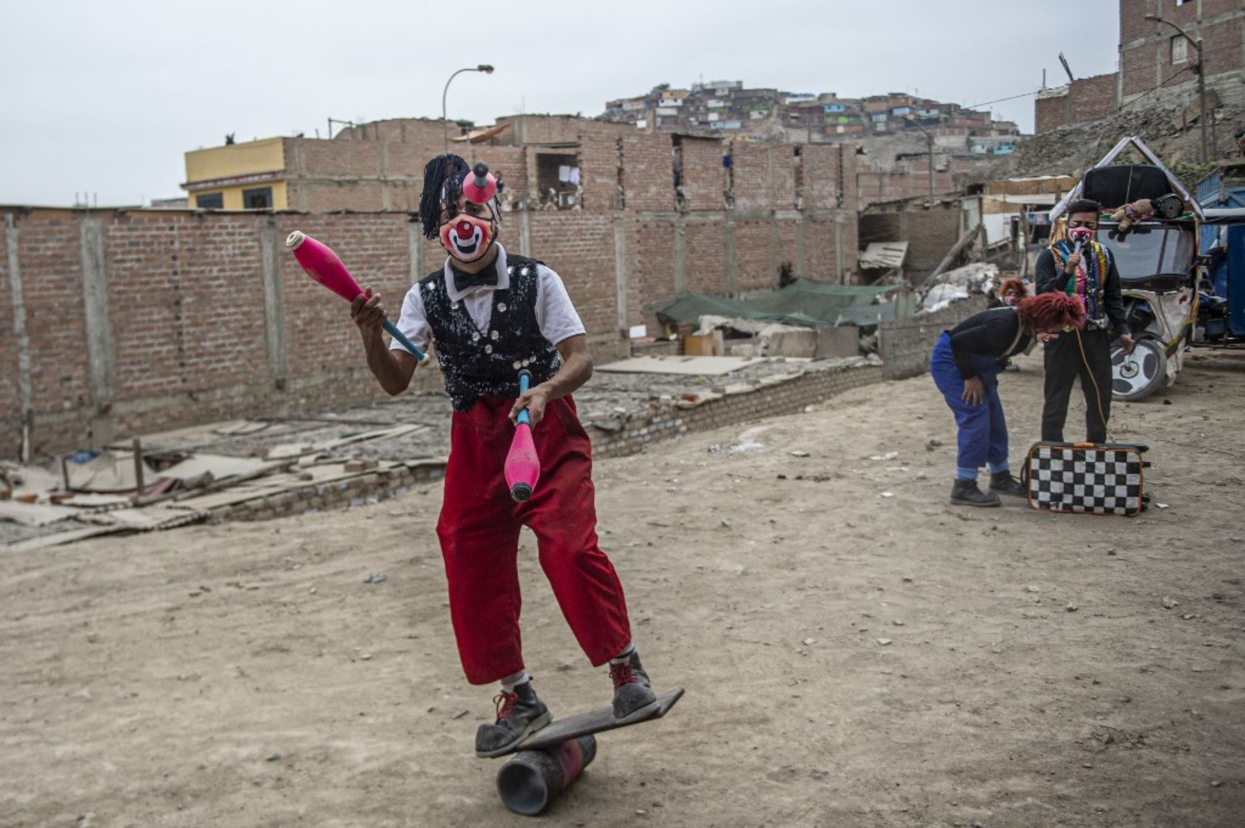 Un payaso con máscara facial actúa en el distrito de Puente Piedra, en las afueras del norte de Lima, durante la pandemia de covid-19.  Debido a la pandemia de coronavirus, los circos en Perú permanecen cerrados, lo que lleva a este grupo de payasos que viajan en su circo mototaxi a actuar en las calles de Lima.   Foto: AFP