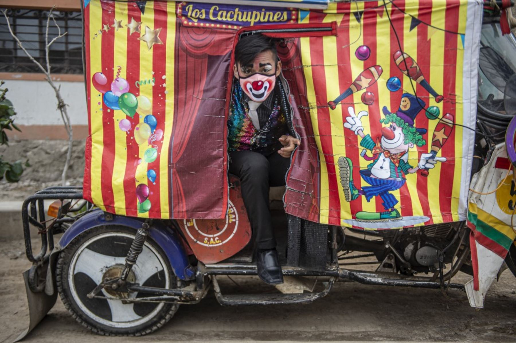 Los payasos con máscaras se presentan en el distrito de Puente Piedra, en las afueras del norte de Lima, durante la pandemia covid-19. - Debido a la pandemia de coronavirus, los circos en Perú permanecen cerrados, lo que lleva a este grupo de payasos que viajan en su circo mototaxi a actuar en las calles de Lima.   Foto: AFP