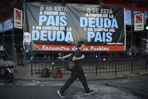 Un hombre pasa junto a una pancarta llamando a rechazar un acuerdo para pagar a los acreedores descontentos. Foto: AFP