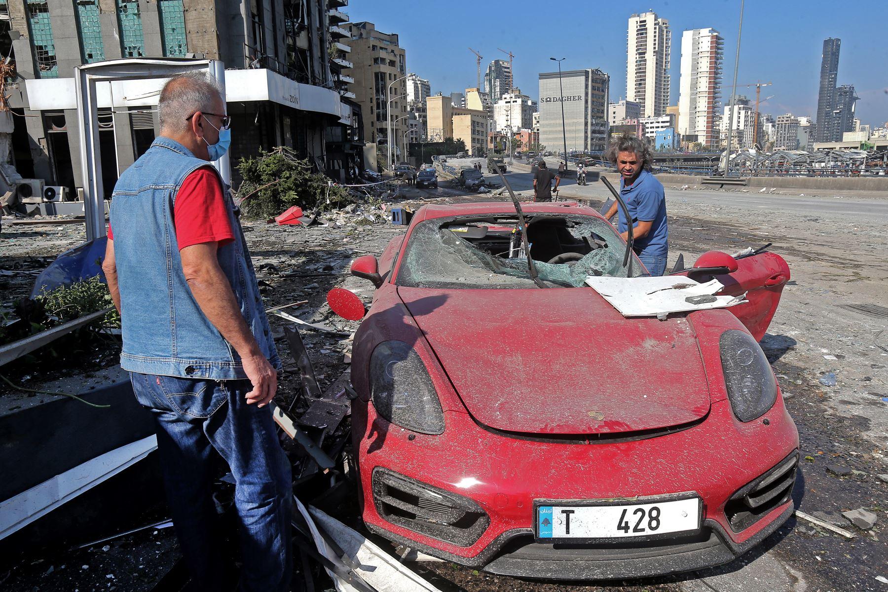 Personas verifican autos y propiedades dañadas a un día de la enorme explosión en el puerto de Beirut. Foto: AFP