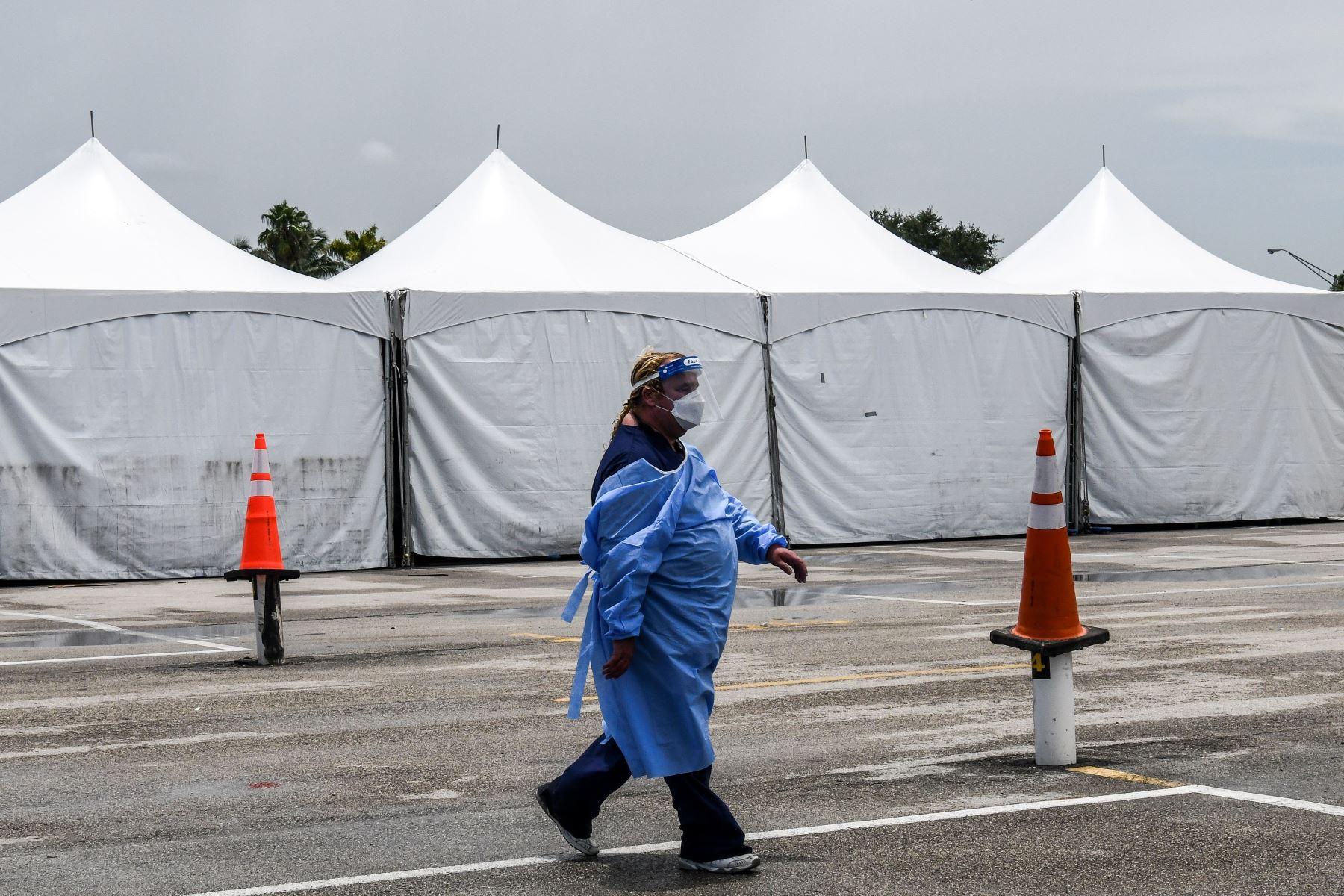 Un miembro del personal médico usa un equipo de protección personal (EPP), que incluye máscaras faciales y escudo, cerca del sitio de prueba rápida de antígeno coronavirus en el Hard Rock Stadium en Miami. Foto: AFP