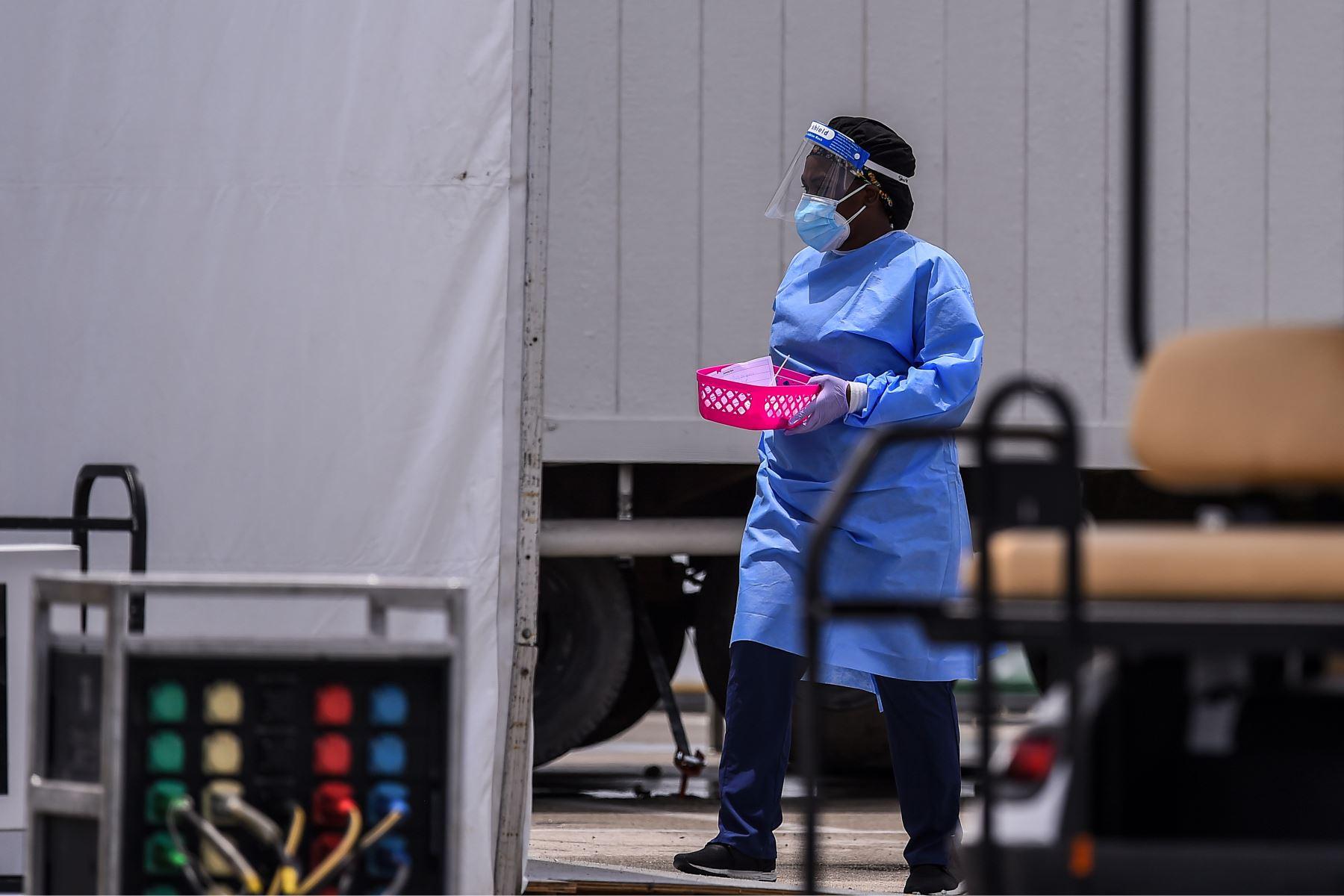 Un miembro del personal médico lleva muestras rápidas de prueba de coronavirus antigénico en el Hard Rock Stadium en Miami. Foto: AFP