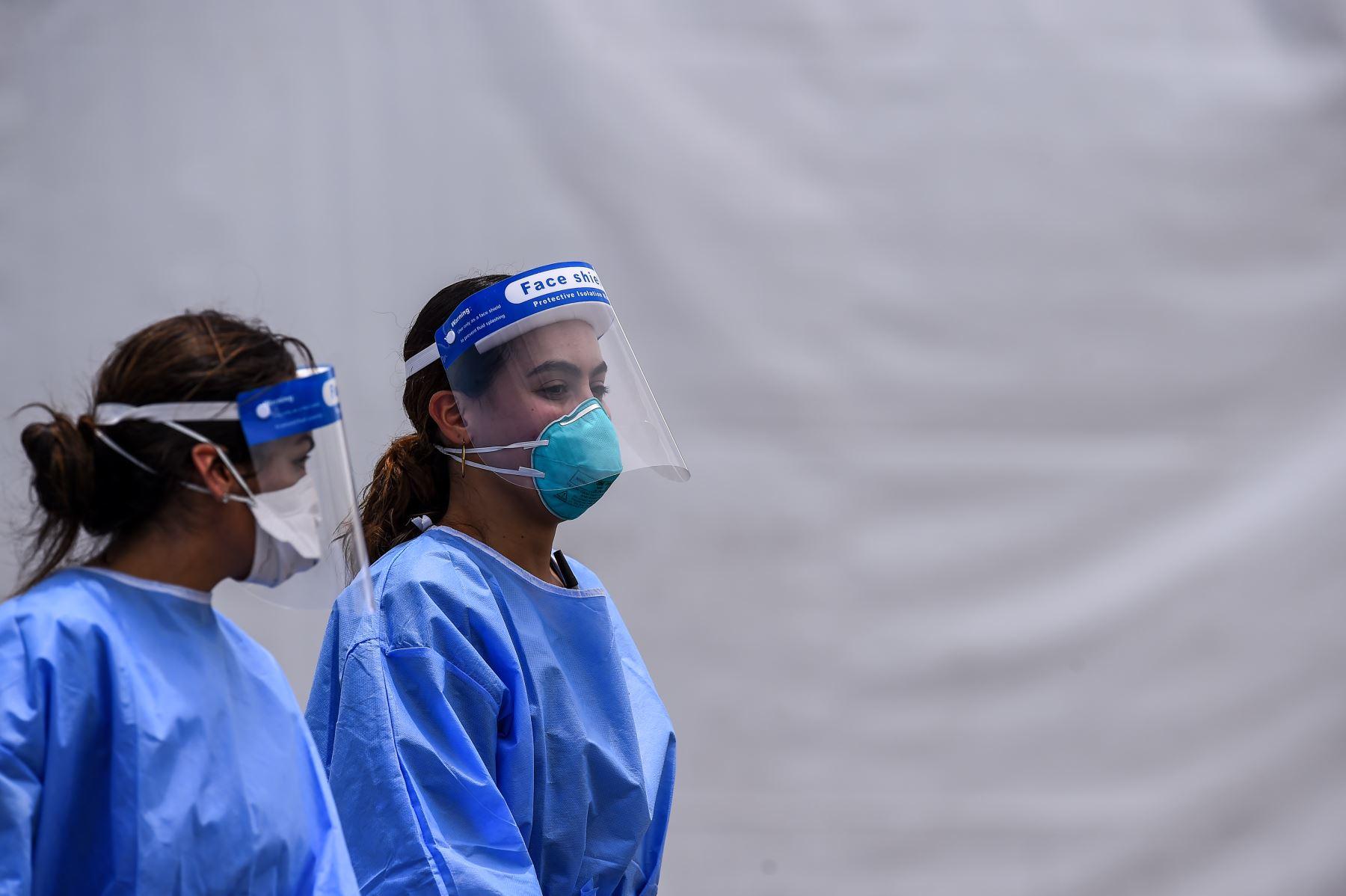 El personal médico usa kits de equipo de protección personal (EPP), que incluyen máscaras faciales y escudos, mientras caminan cerca del sitio de prueba rápida de antígeno del coronavirus en el Hard Rock Stadium en Miami. Foto: AFP