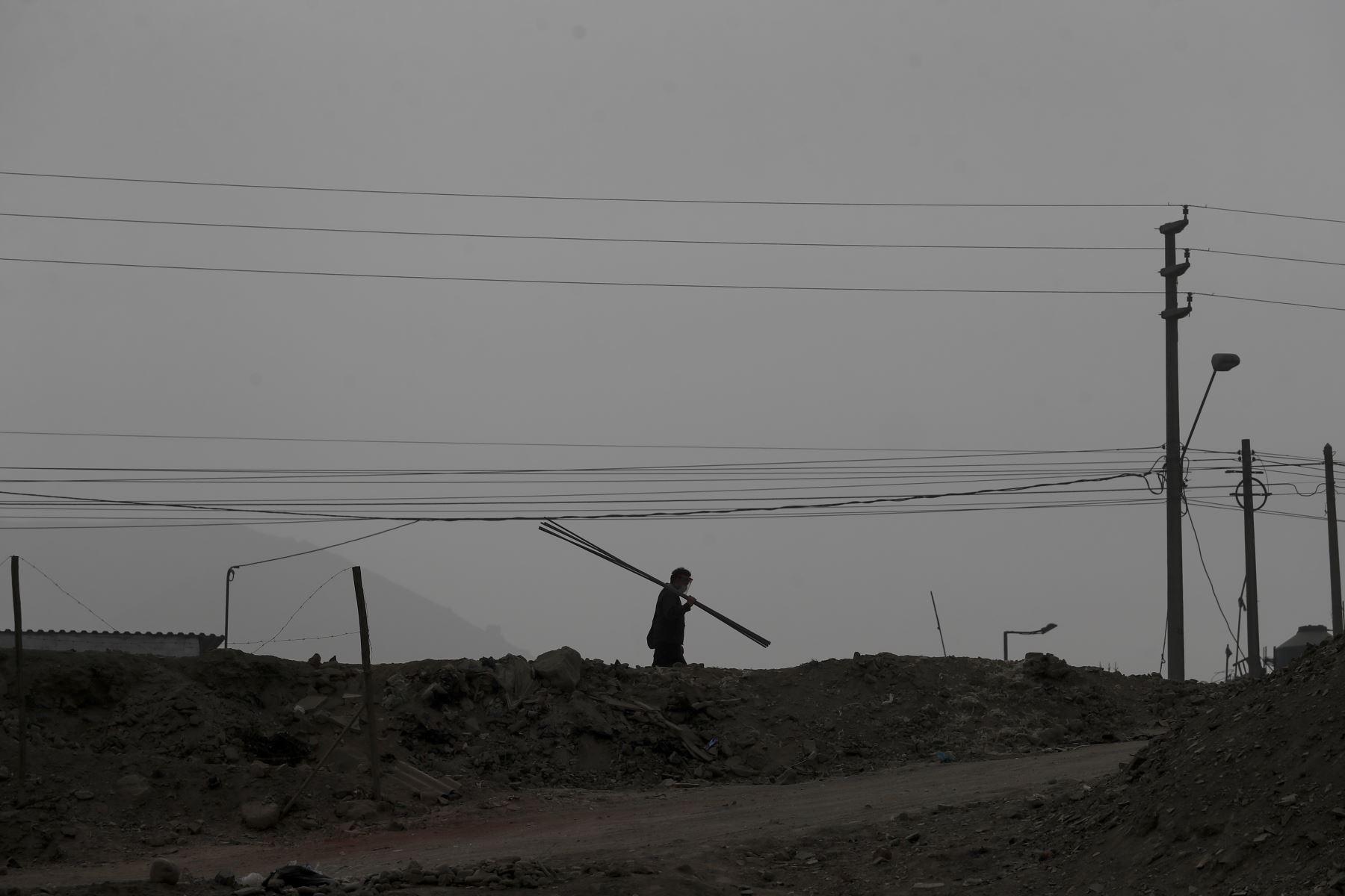 Un trabajador camina con protector facial por las lomas de Manchay. Foto: ANDINA/Renato Pajuelo