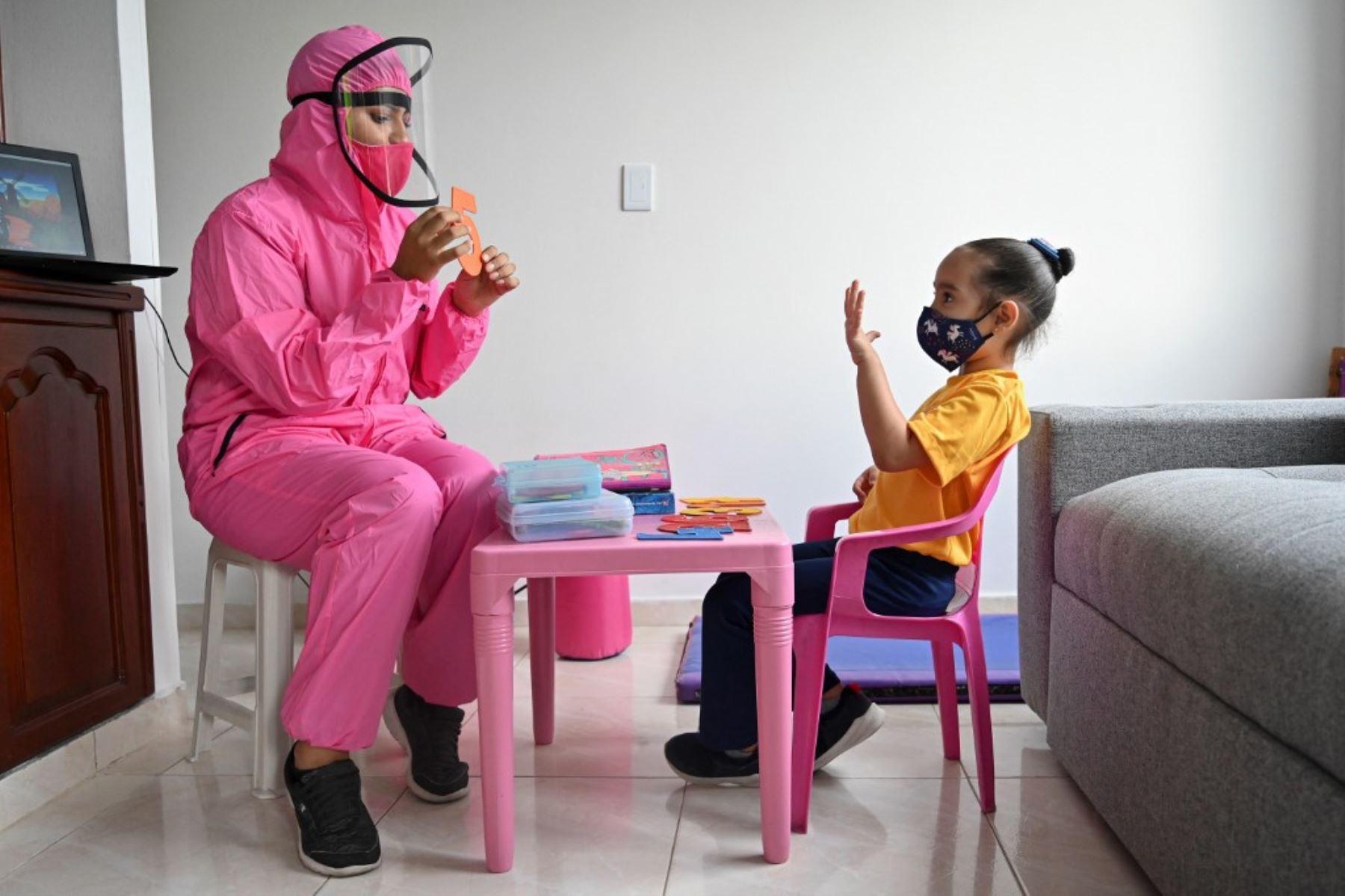 Una maestra que usa un traje de bioseguridad como medida preventiva contra la propagación del nuevo coronavirus, covid-19, da una clase a una niña en su casa en Cali, Colombia. Foto: AFP