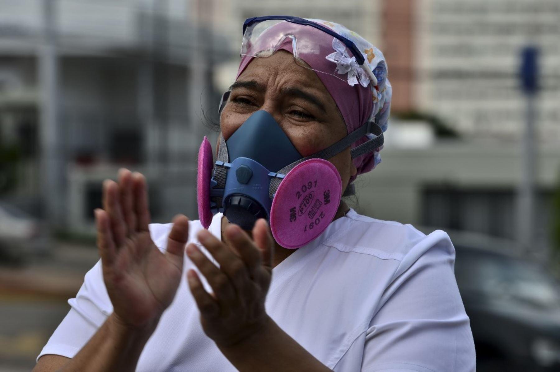 Un colega aplaude durante el funeral de un enfermero del Instituto Hondureño de Seguridad Social, que murió de covid-19, en Tegucigalpa. Foto: AFP