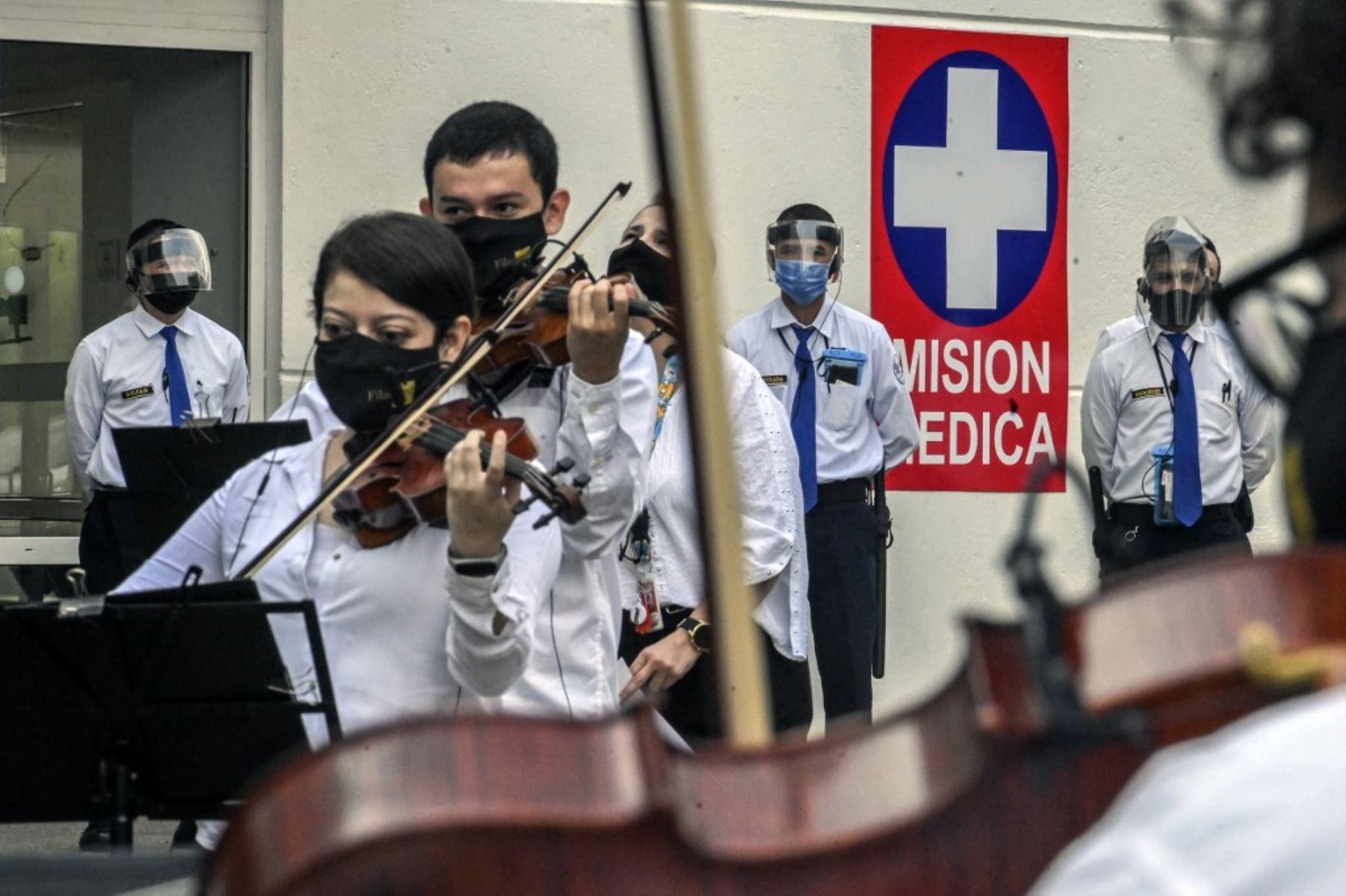 Trabajadores de la salud, pacientes y familiares miran a músicos de la Orquesta Filarmónica de Medellín tocando frente a un hospital, en medio de la pandemia covid-19, en Medellín. Foto: AFP