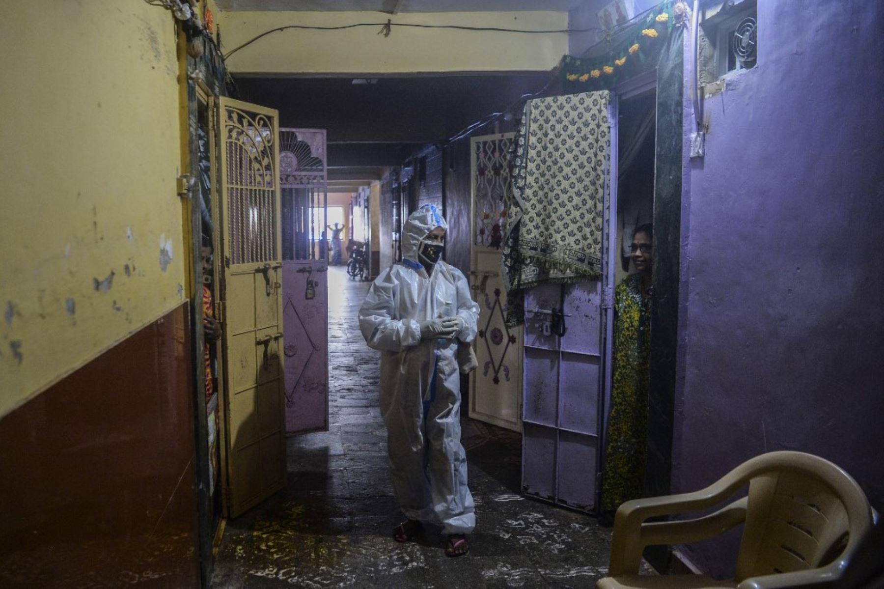 Un trabajador de la salud que usa un traje de Equipo de Protección Personal interactúa con un residente durante un examen de coronavirus covid-19 puerta a puerta en el área de los barrios marginales de Dharavi en Mumbai. Foto: AFP
