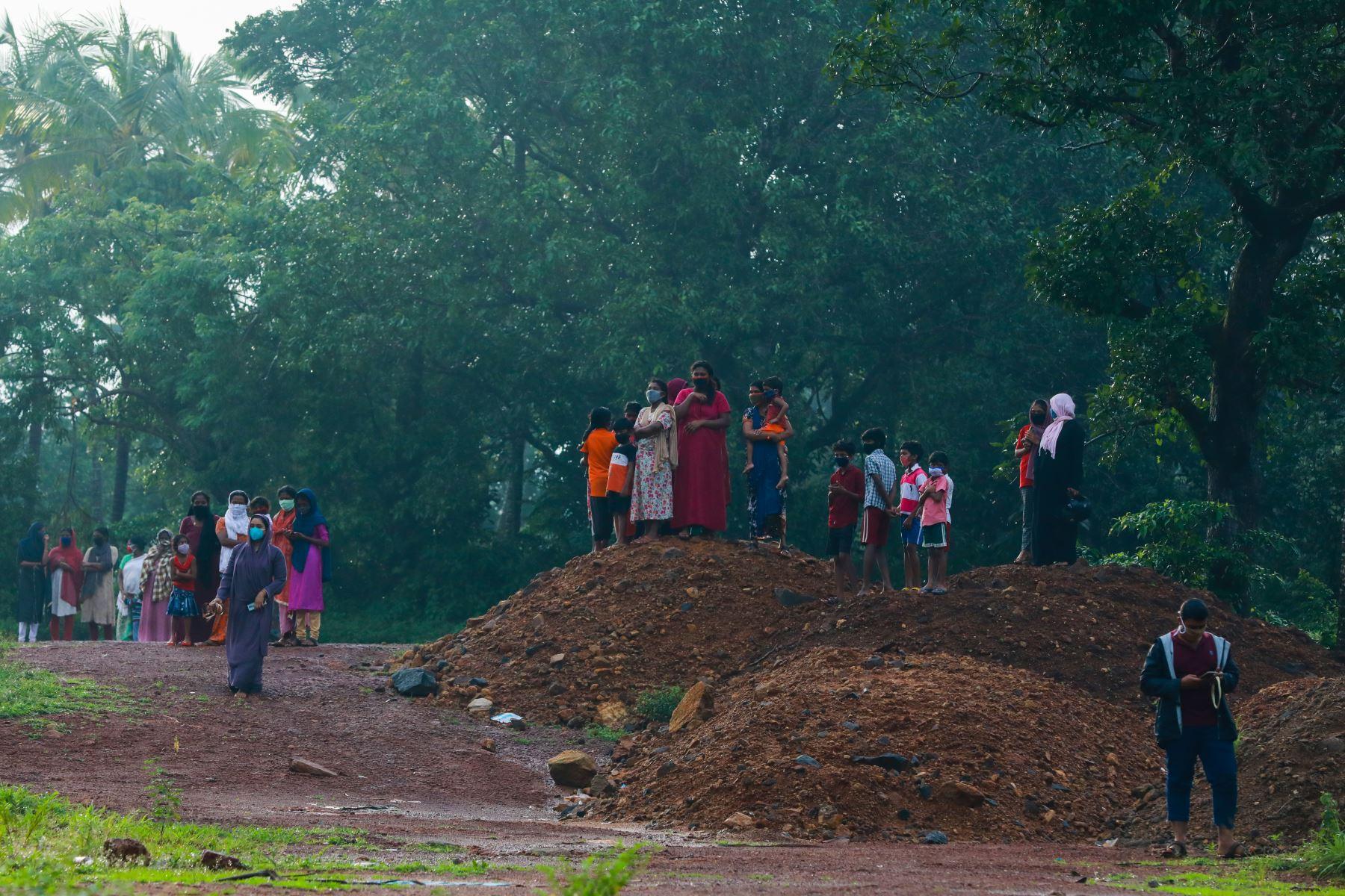 Un grupo de personas observan la inspección los restos del avión de Air India Express tras sufrir accidente. Foto: AFP