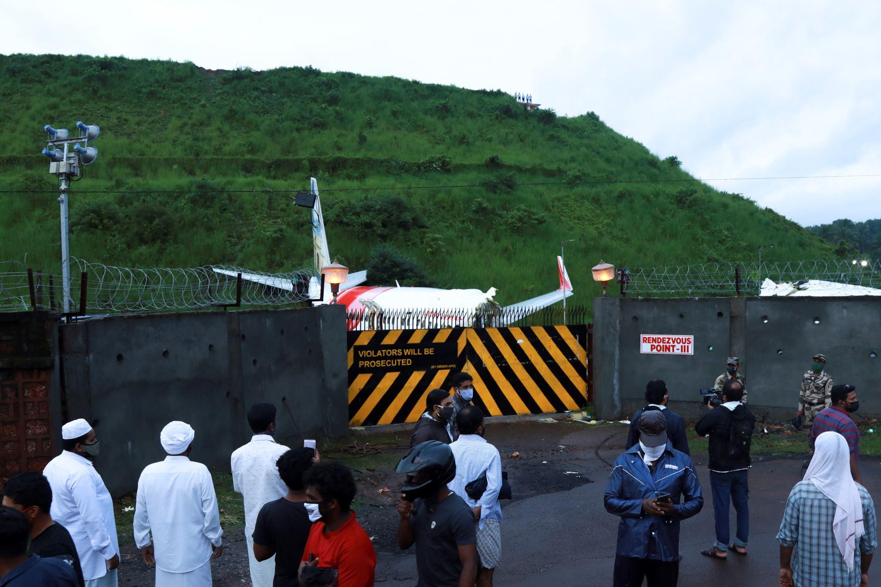 La gente se reúne frente a la puerta donde se encuentras los restos del Air India Express en el Aeropuerto Internacional de Calicut en Karipur, Kerala. Foto: AFP